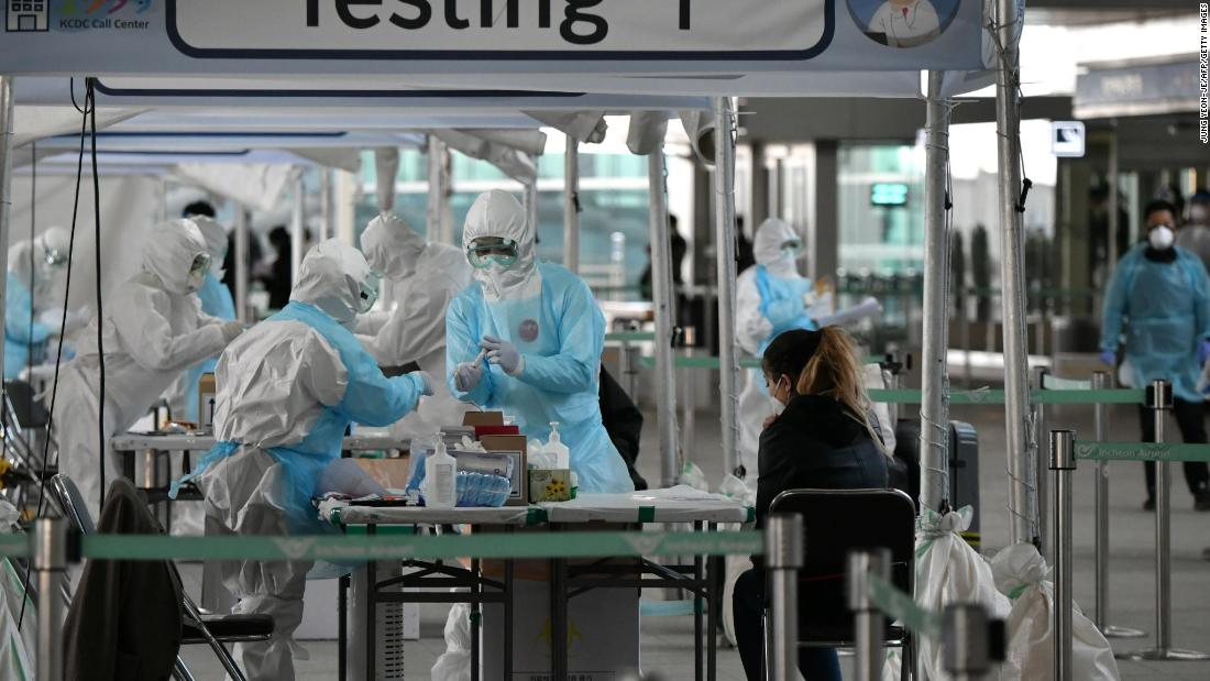 Medical staff wearing protective clothing take test samples for the coronavirus from a passenger at a virus testing booth outside Incheon International Airport, west of Seoul, on April 1.