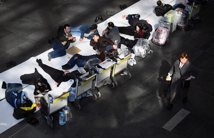 People sit stuck at Moscow's Vnukovo airport on March 24 after neighboring countries closed borders and stopped flights.