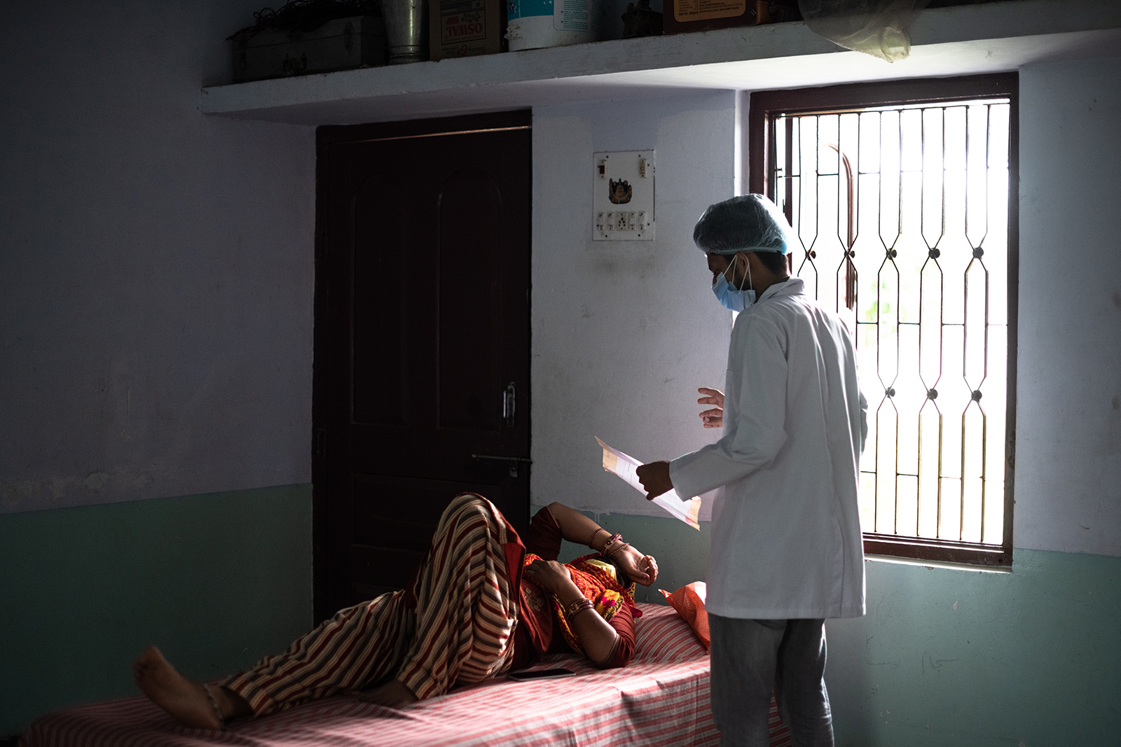 A medical assistant speaks with a patient at a makeshift clinic and quarantine center for people with Covid-19 at the Jamia Arabia Barkatul Islam seminary on May 18, in Laxmangarh, Sikar district of Rajasthanstate, India.