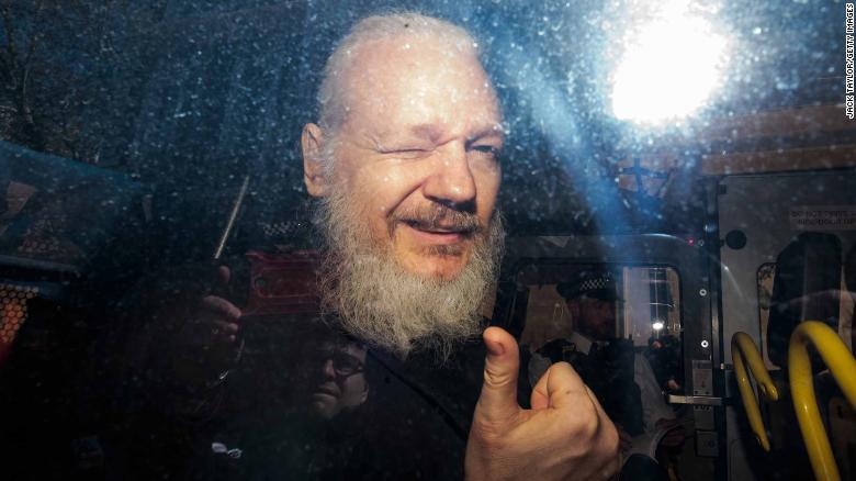 Julian Assange gives a thumbs up to onlookers from inside a police van in London on Thursday.