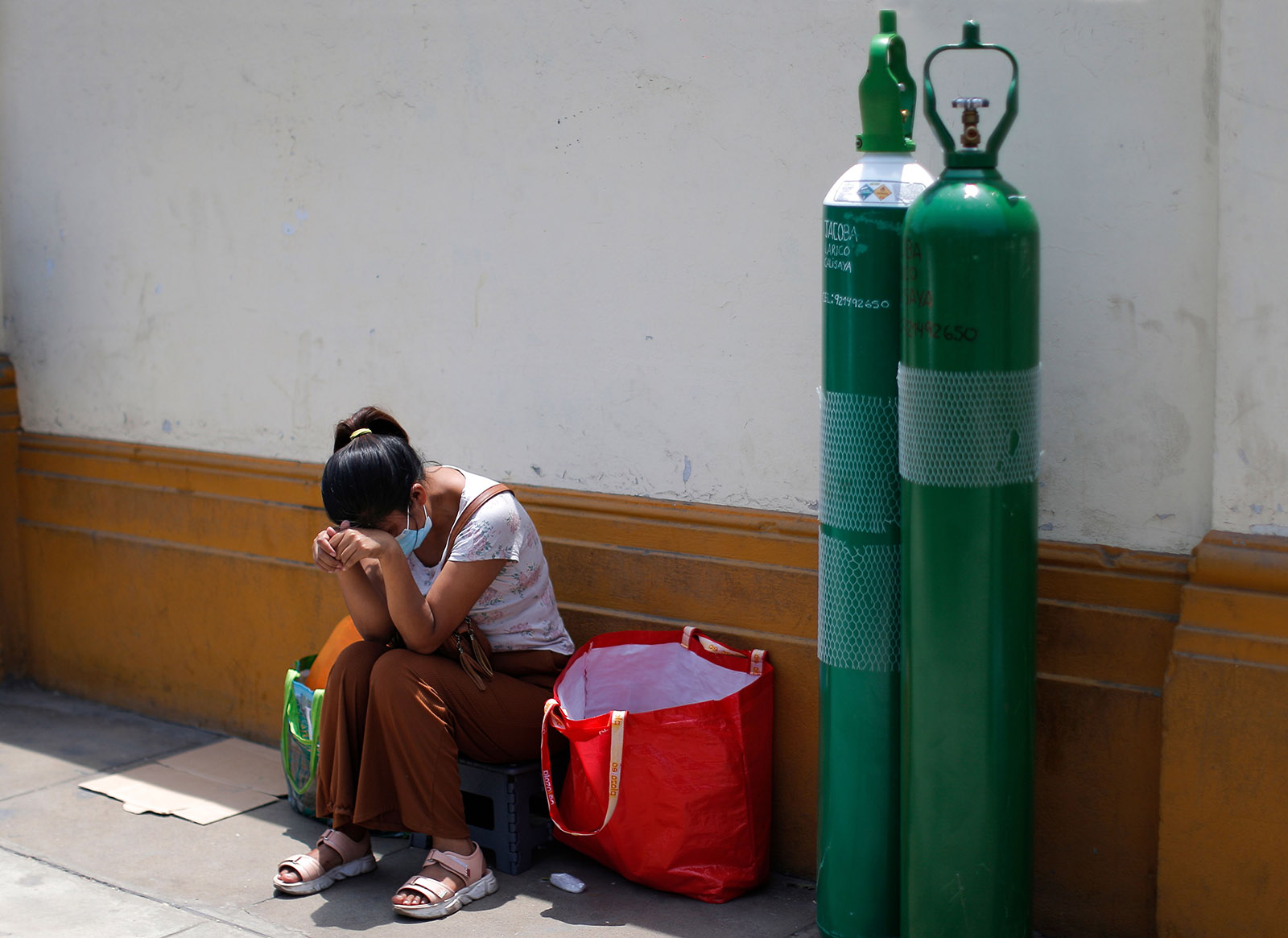 Relatives of Covid-19 victims queue to refill oxygen tanks, in Lima, Peru on February 9, 2021.
