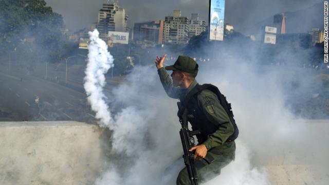A member of the Bolivarian National Guard supporting Venezuelan opposition leader and self-proclaimed acting president Juan Guaido throws a tear gas canister during a confrontation with guards loyal to President Nicolas Maduro's government in front of La Carlota military base in Caracas.