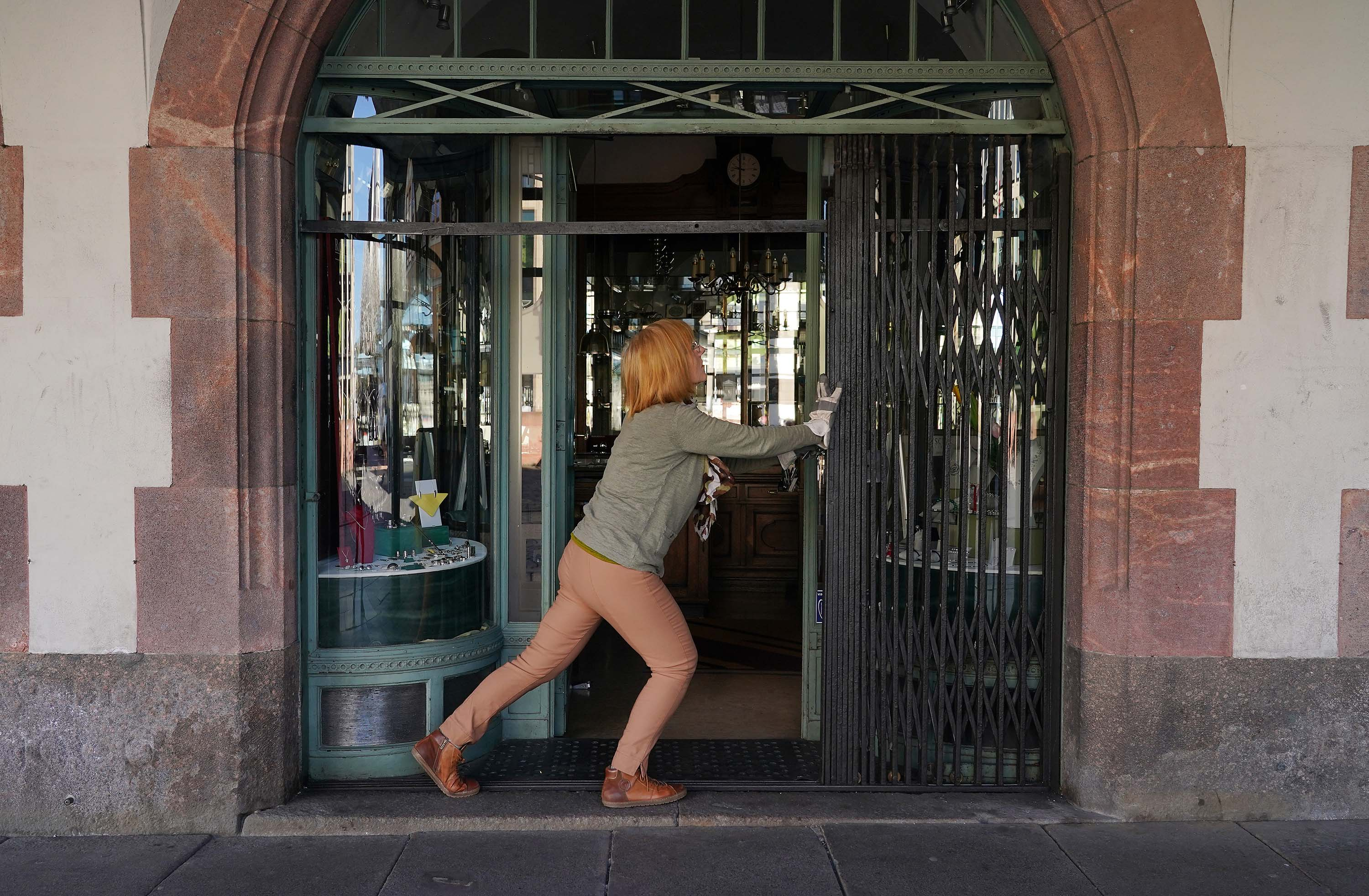 A shopkeeper pushes open a shutter prior to opening her antiques store for the first time since March, on April 20, in Leipzig, Germany.