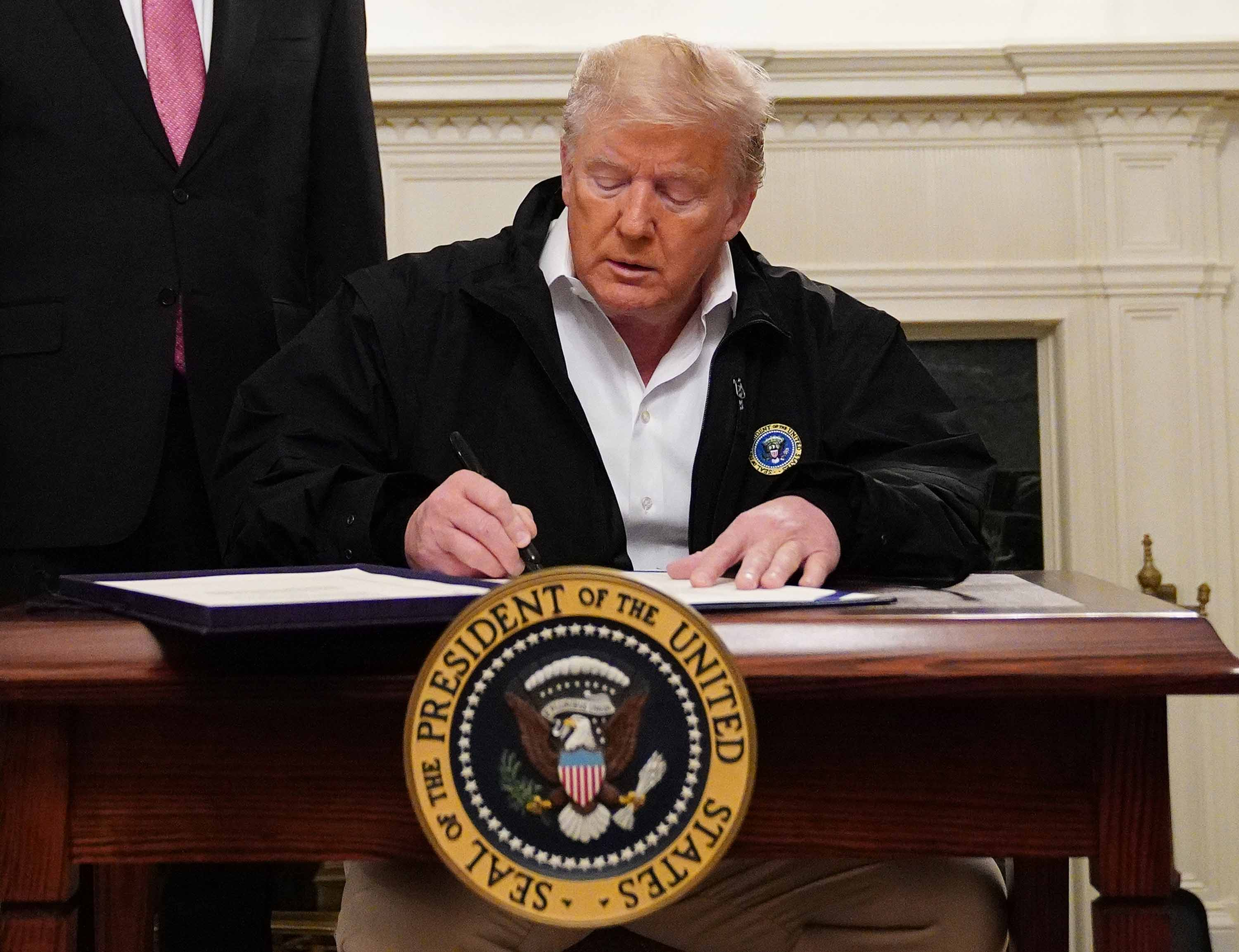 President Donald Trump signs an emergency funding bill to combat the coronavirus outbreak on Friday.