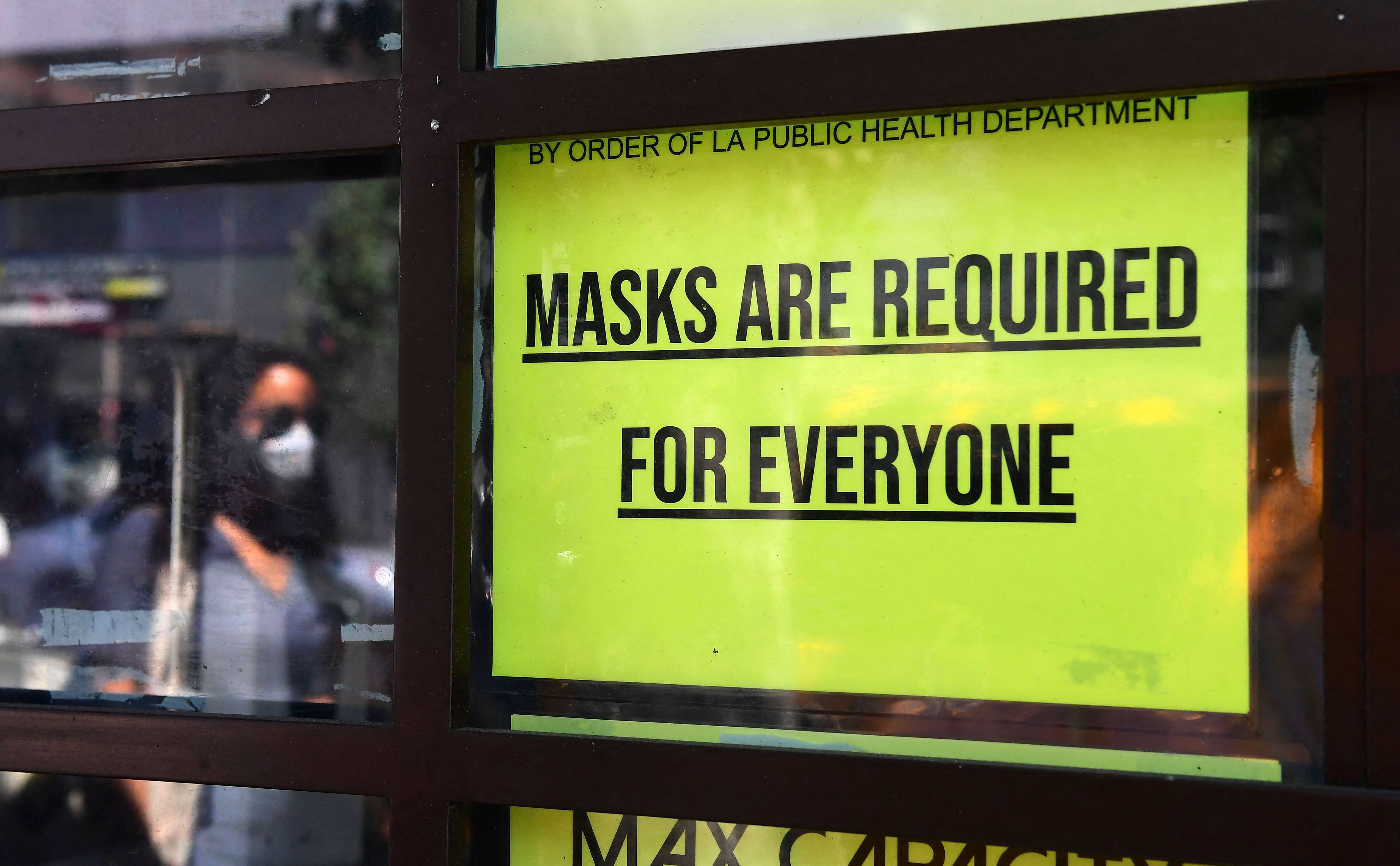 A sign about mask requirements is on a storefront in Los Angeles on July 19, 2021.