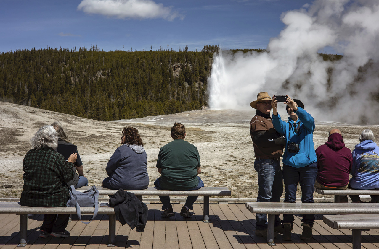 Tourists watch Old Faithful erupt in Yellowstone National Park on Thursday, April 29, in Wyoming.
