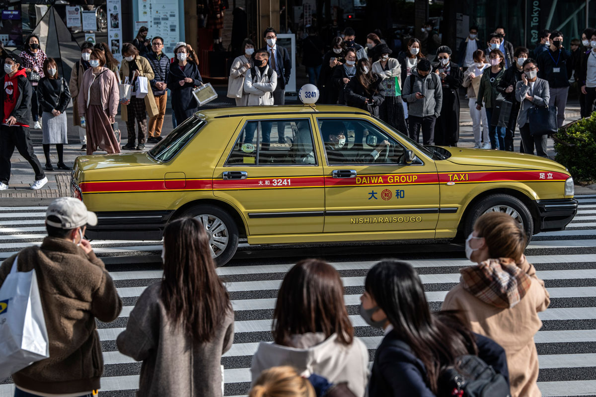 People wait to cross a road as a taxi drives past on November 11 in Tokyo, Japan.