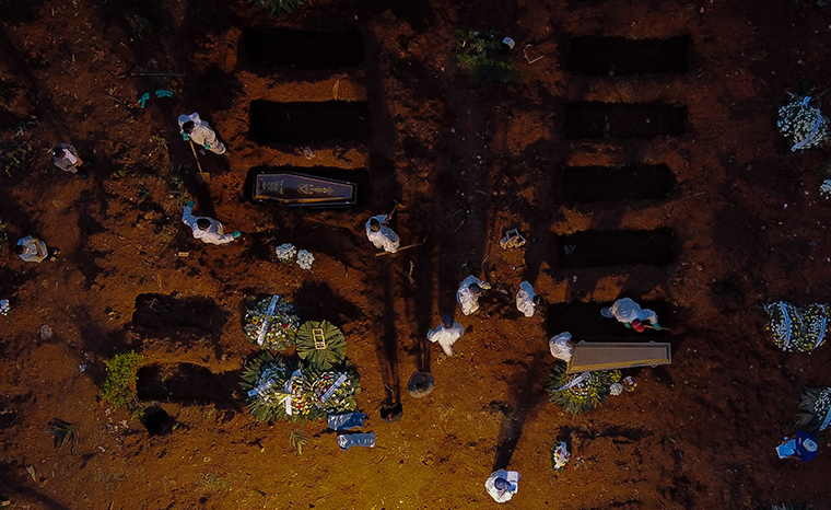 Workers in protective gear as a preventive measure against the spread of the novel coronavirus disease bury coffins at the Vila Formosa cemetery in Sao Paulo, Brazil, on April 17, 2021.