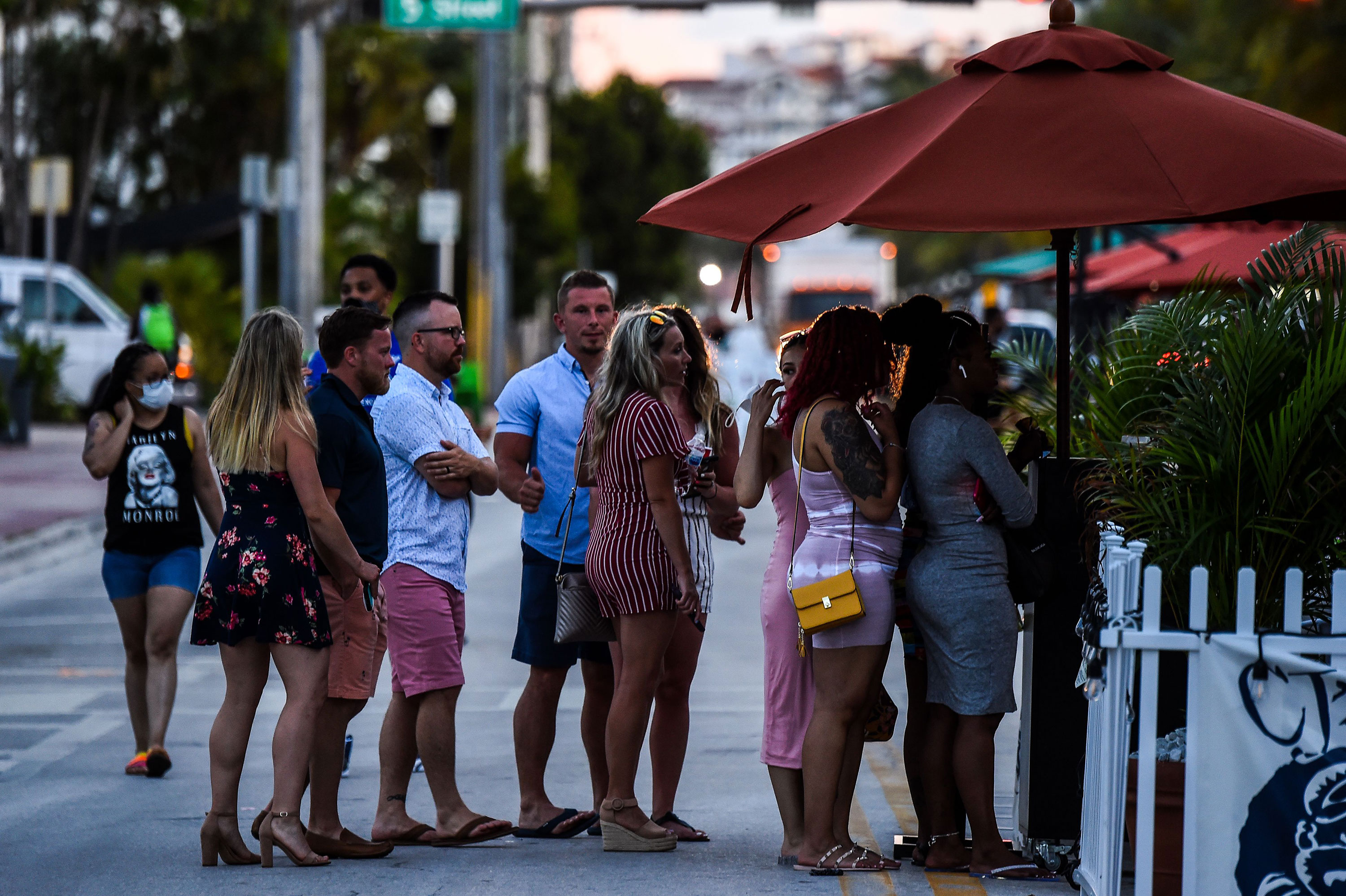 People stand in line at a restaurant on Ocean Drive in Miami Beach, Florida, on June 26.