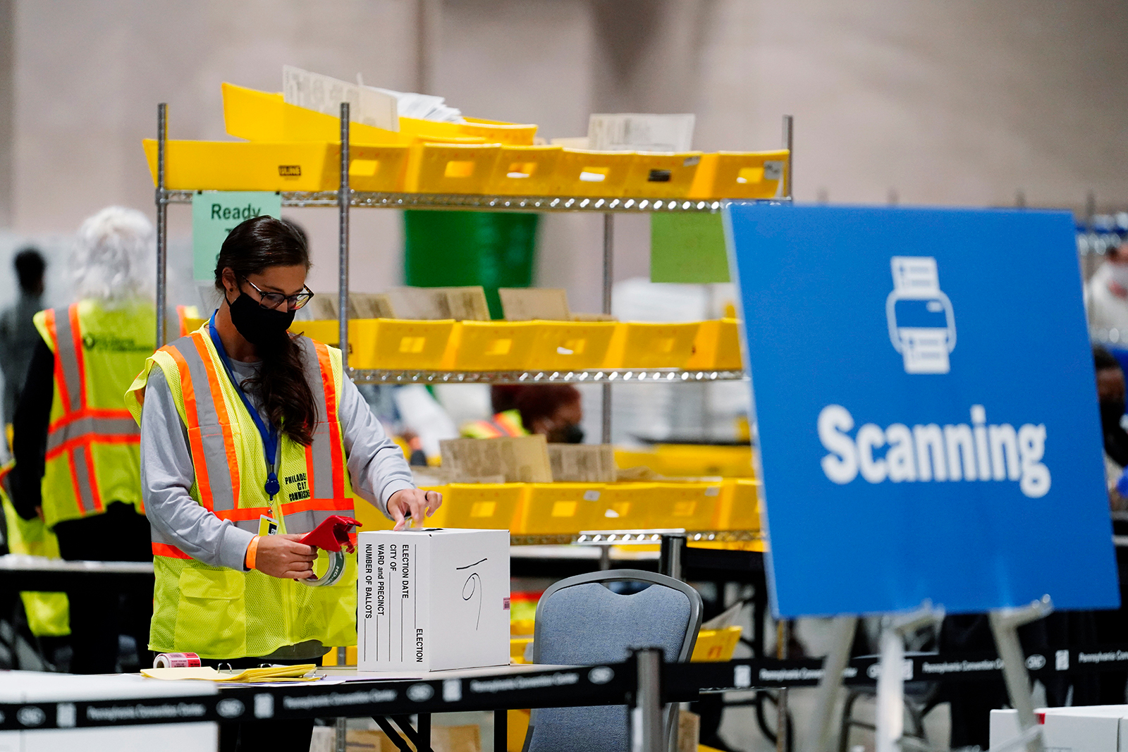 A Philadelphia election worker processes mail-in and absentee ballots for the 2020 general election in the United States at the Pennsylvania Convention Center, Tuesday, Nov. 3, in Philadelphia.