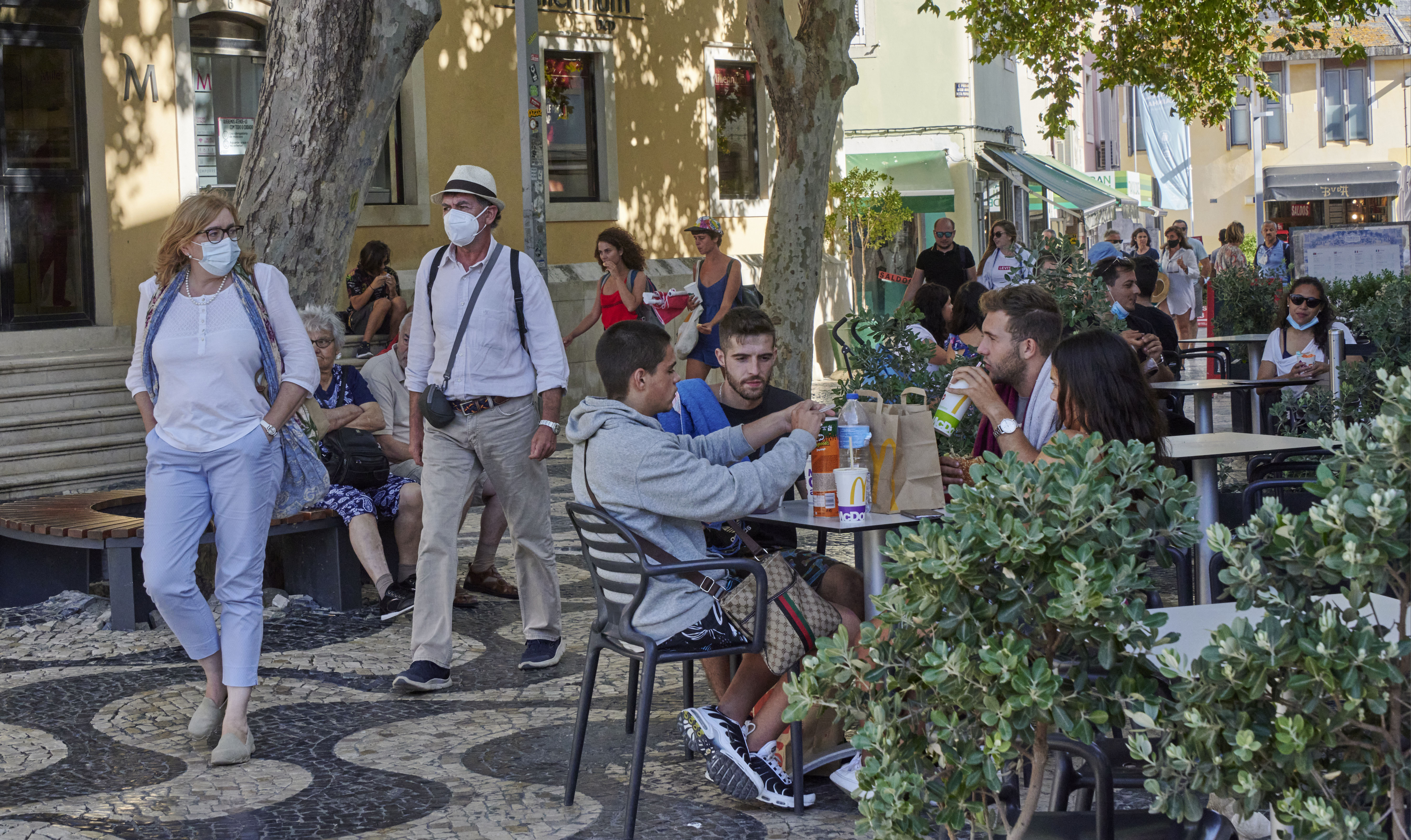 People spend time outside in Cascais, Portugal, on August 9.