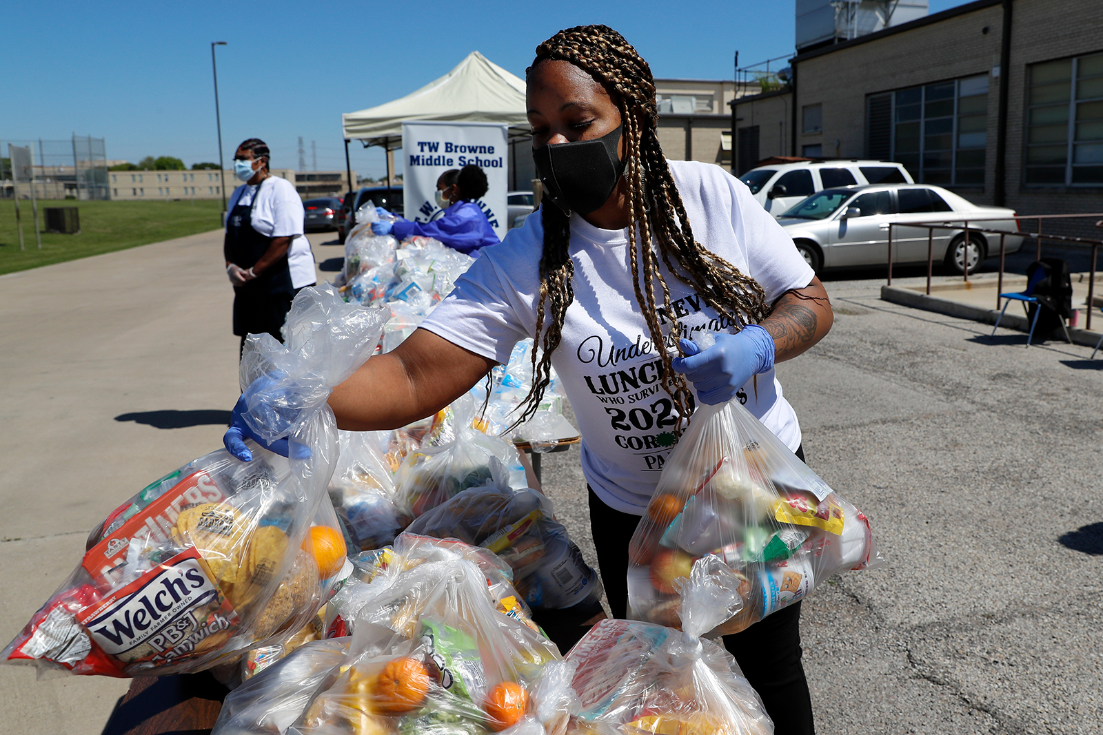 T.W. Browne Middle School food service employee Keke LaFayette, prepares to distribute food to a Dallas Independent School District family in Dallas, on April 16.