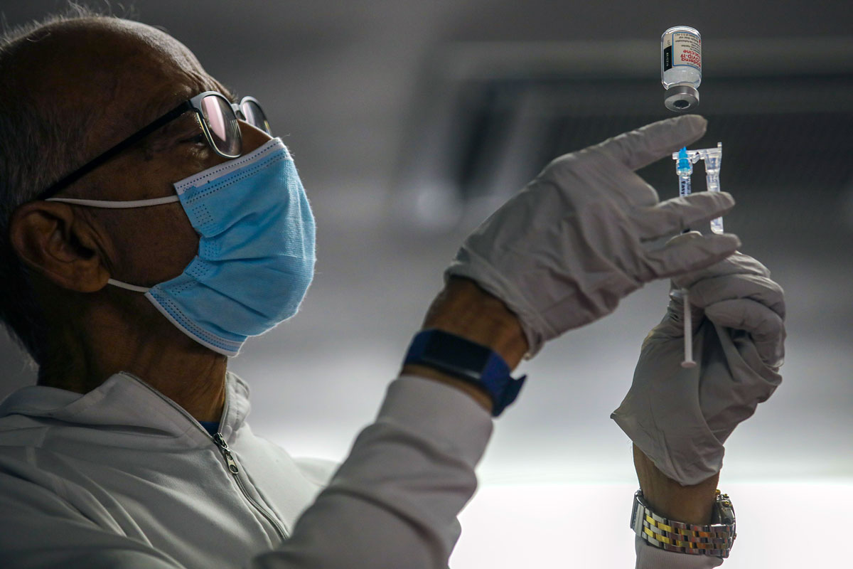 A doctor prepares vaccines for a Covid-19 vaccine clinic at a Hindu temple Sanatan Dharma Temple on Saturday, May 8 in Norwalk, CA.