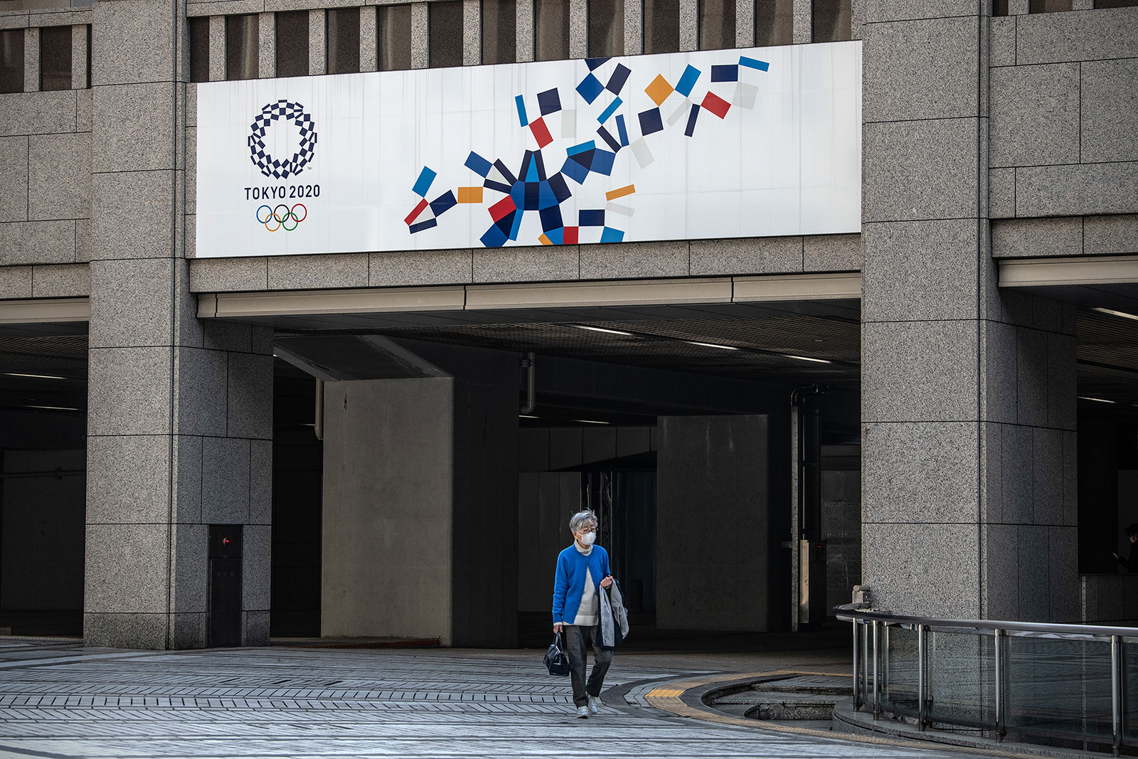 A woman walks beneath a Tokyo 2020 banner on March 19, in Tokyo, Japan.