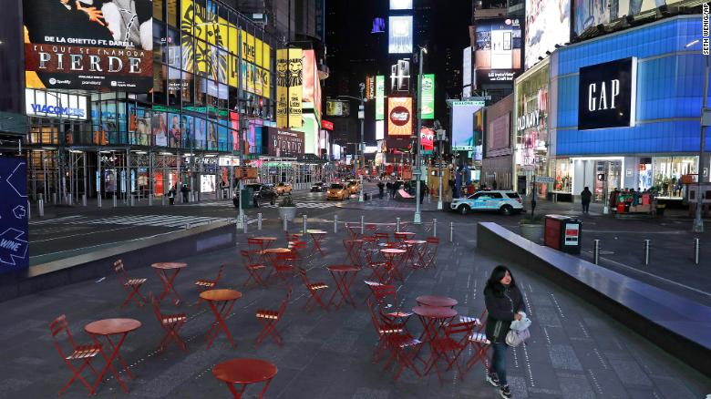 A woman walks through a lightly trafficked Times Square in New York on Monday.