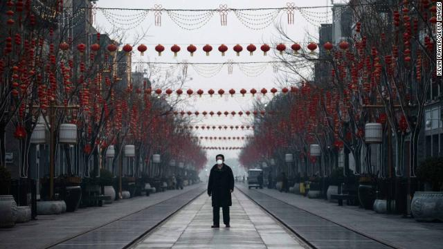 A Chinese man wears a protective mask as he walks in a nearly empty and shuttered commercial street in Beijing.