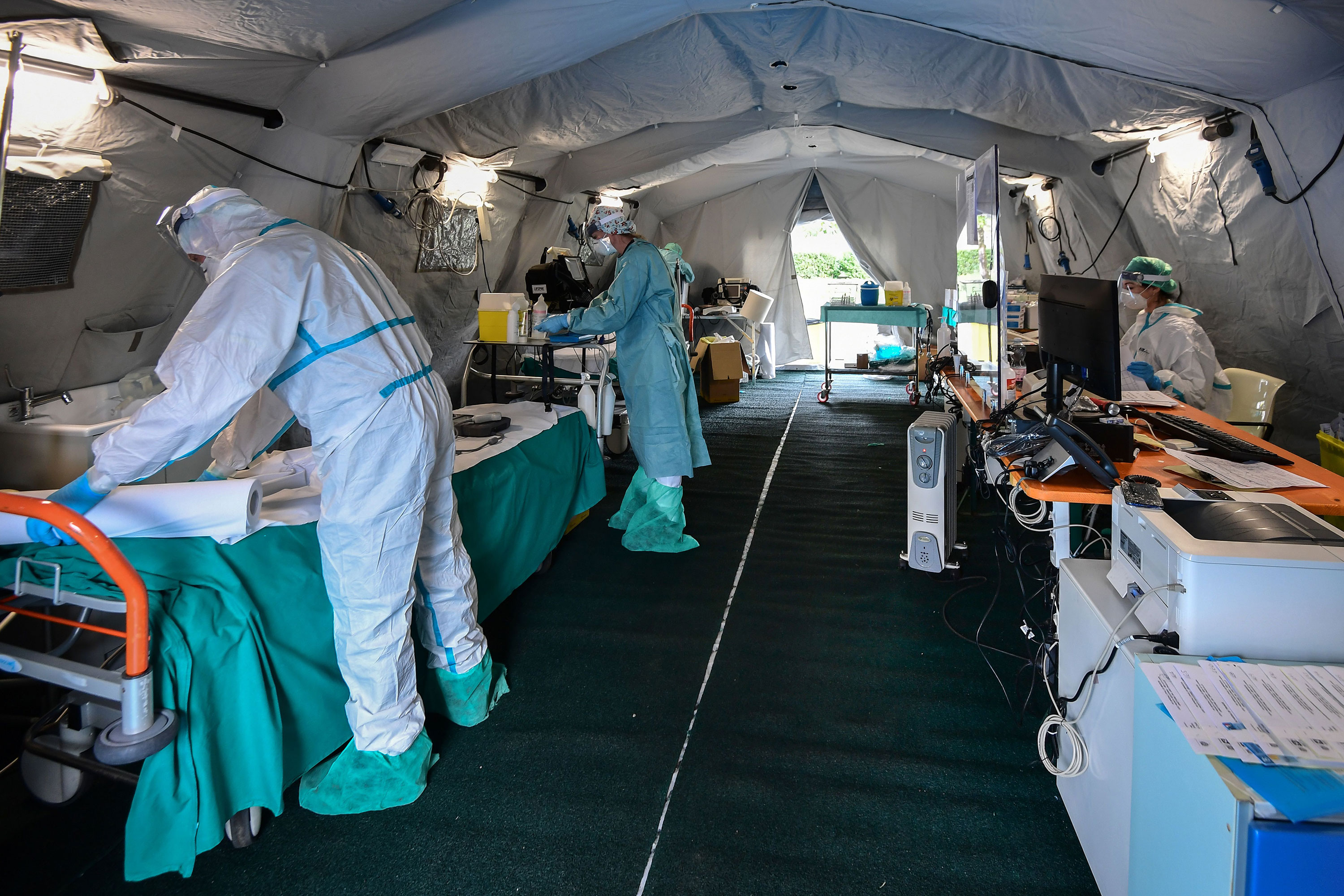 Hospital workers wearing protective masks and gear work in a patients' triage tent at a temporary emergency structure set up outside a hospital in Brescia, Italy, on March 13.
