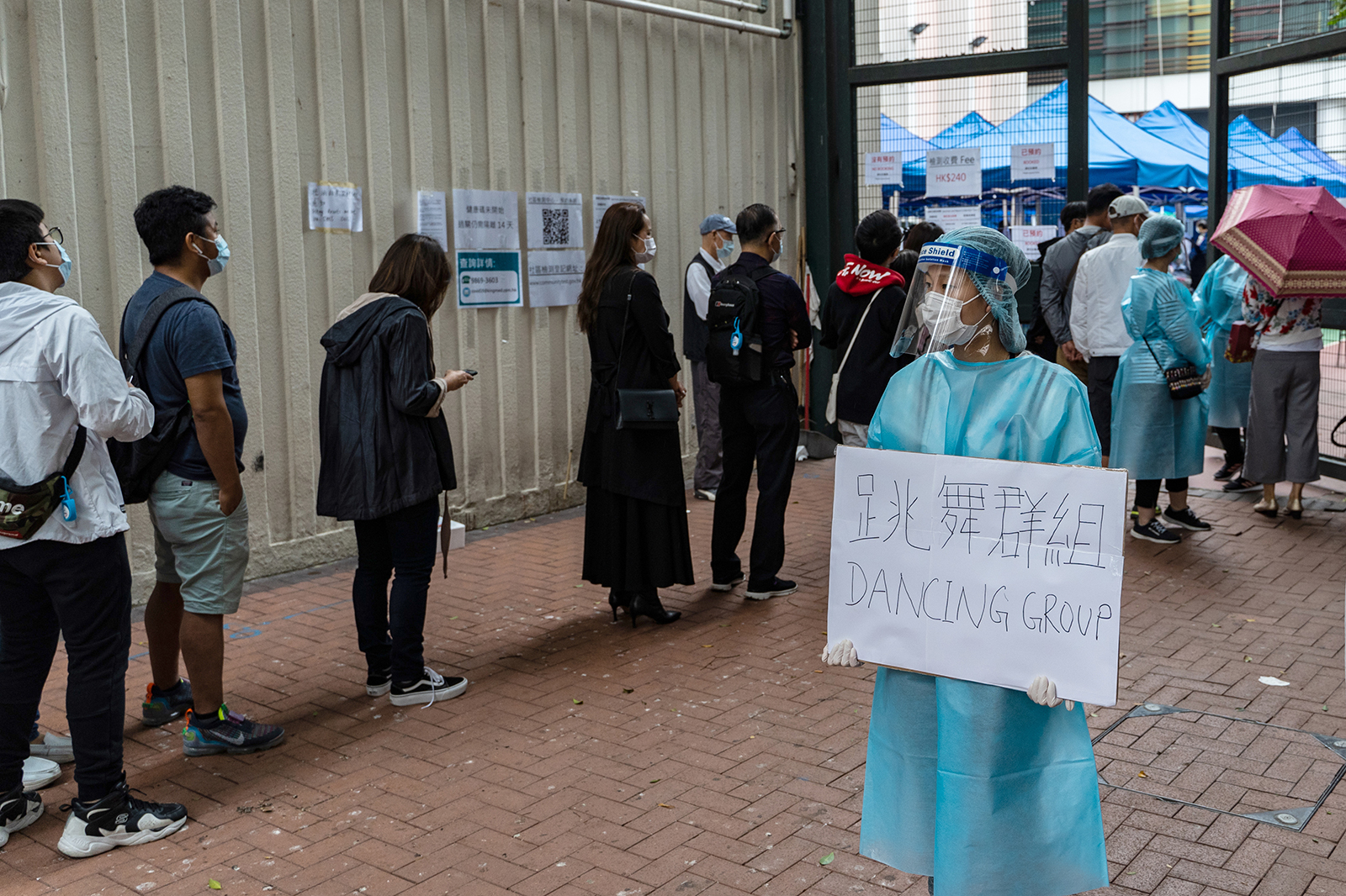 """A health care worker holds a sign reading """"Dancing Group,"""" referring to a dance club cluster of Covid-19, as people stand in line outside a testing center in the Yau Ma Tei district of Hong Kong, on November. 23."""