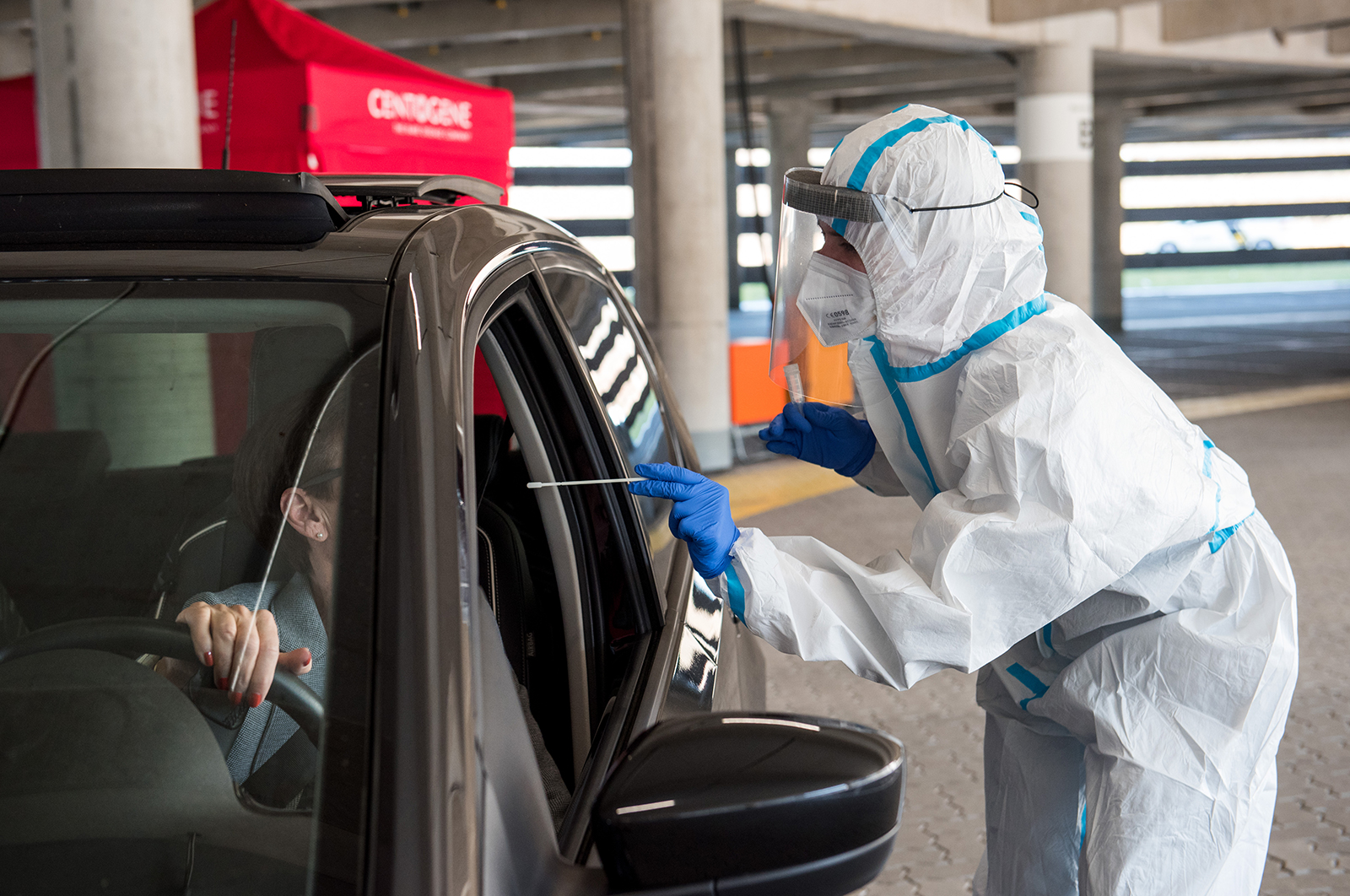 An employee takes a swab from a woman for a Covid-19 test during a trial run for a drive-through Covid-19 testing center at the airport in Hamburg, Germany, on March 31.