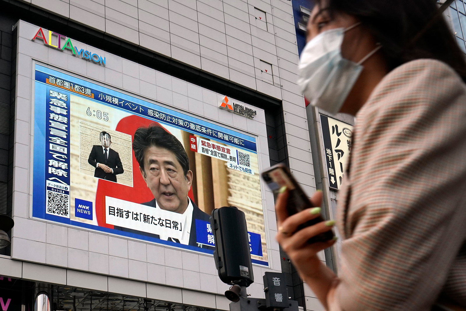 A public screen shows Japanese Prime Minister Shinzo Abe speaking at a press conference in Tokyo, on May 25. Abe lifted a coronavirus state of emergency in Tokyo.