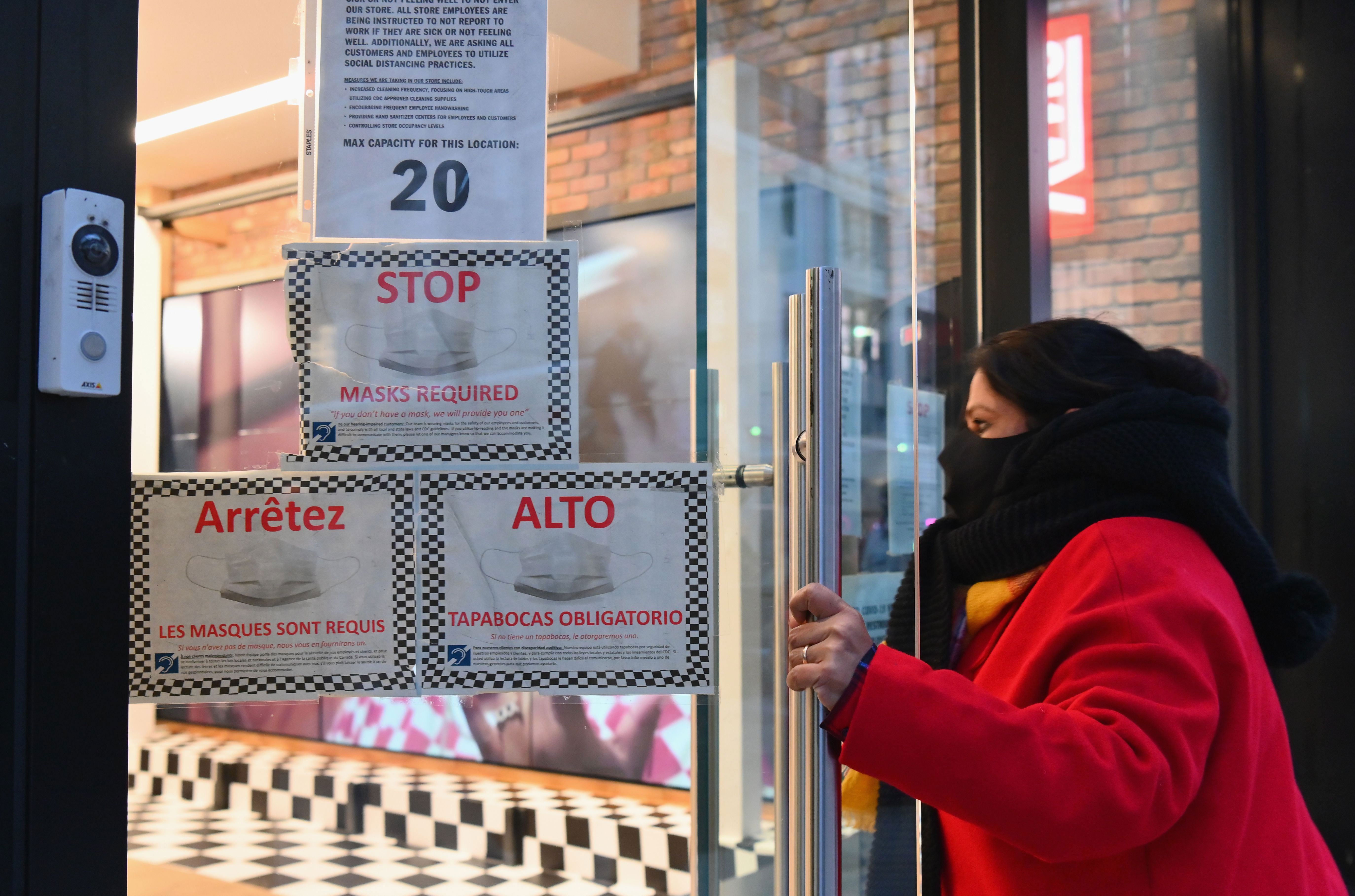 A person opens a door that has signs about masks in New York on January 8.