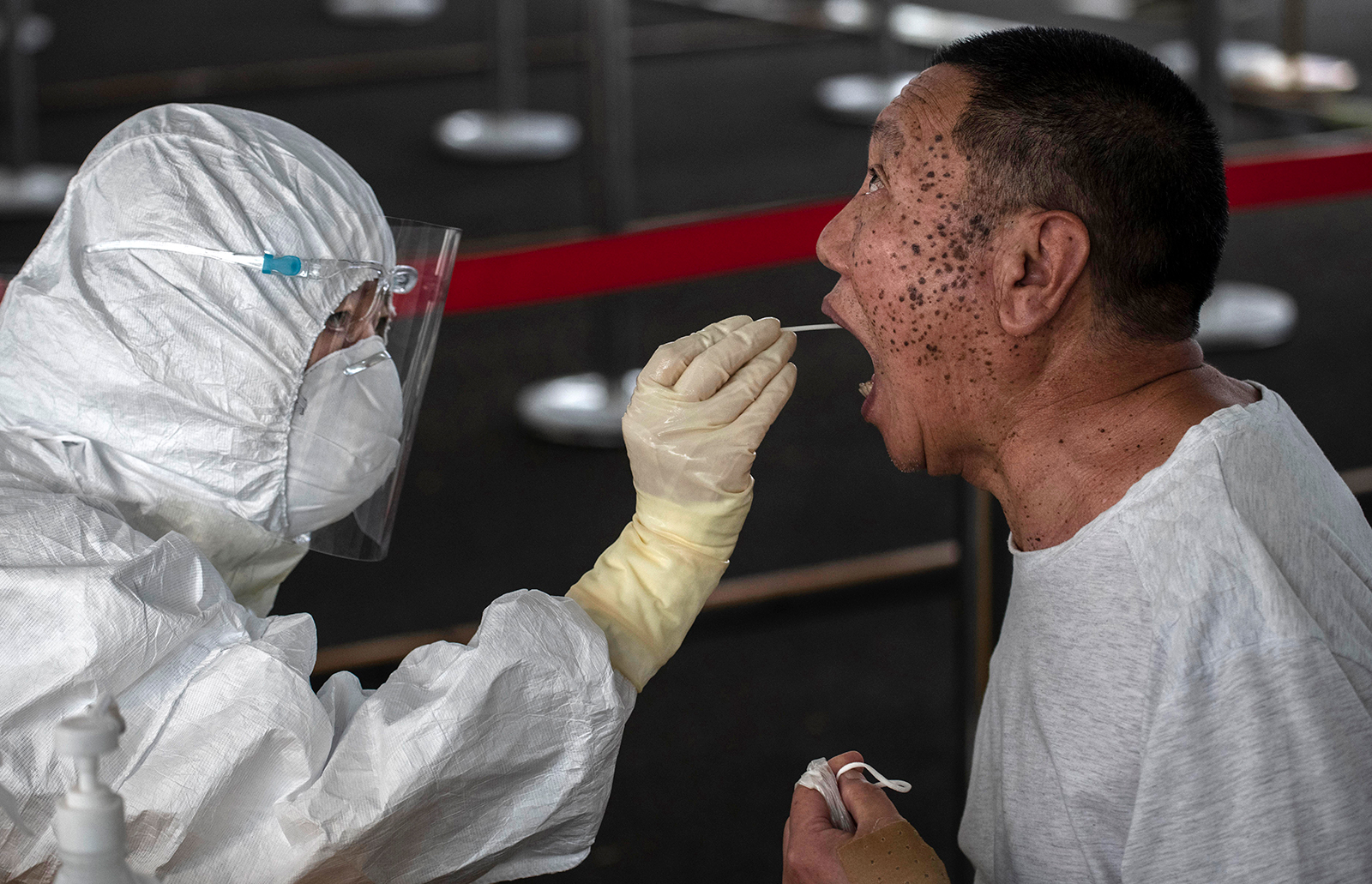An epidemic control worker wears a protective suit as they perform a nucleic acid swab test for Covid-19 on June 24, in Beijing.