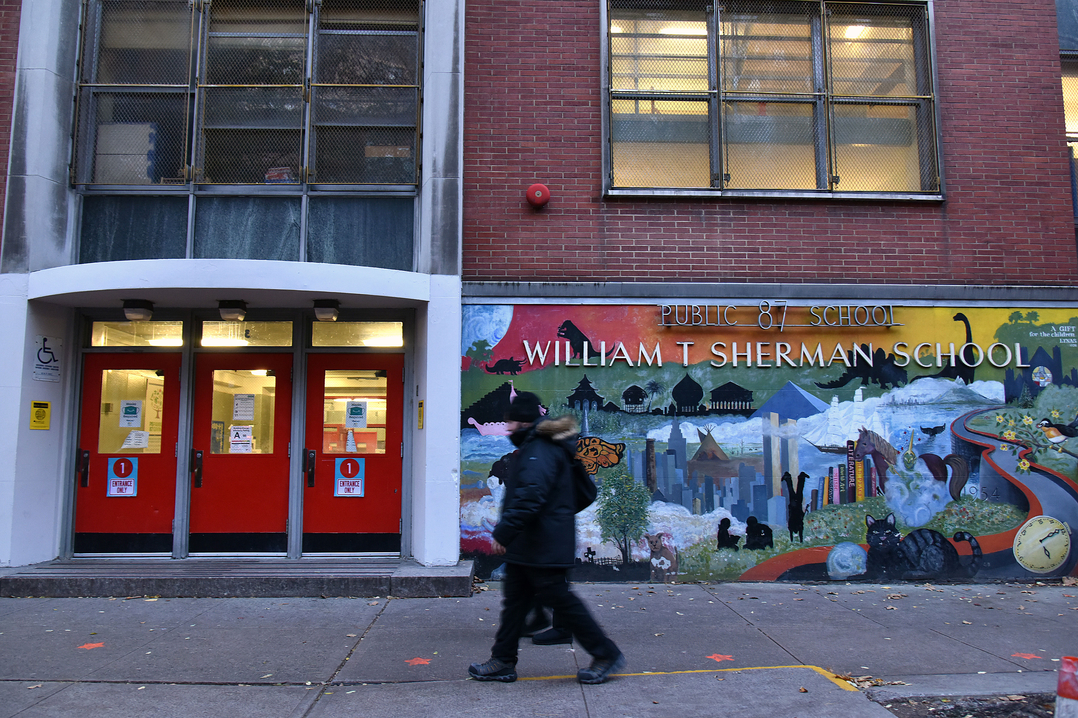 People walk past a public school in New York on November 18.