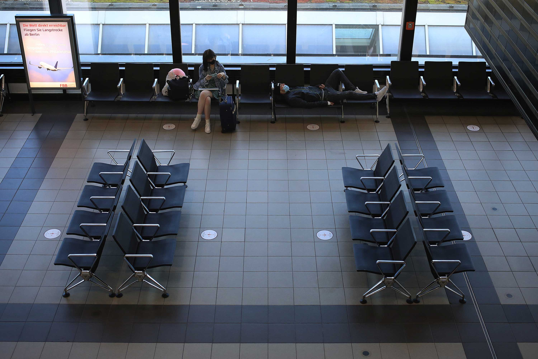 Travelers wait in a departure lounge at Berlin Shoenfeld Airport on June 15.