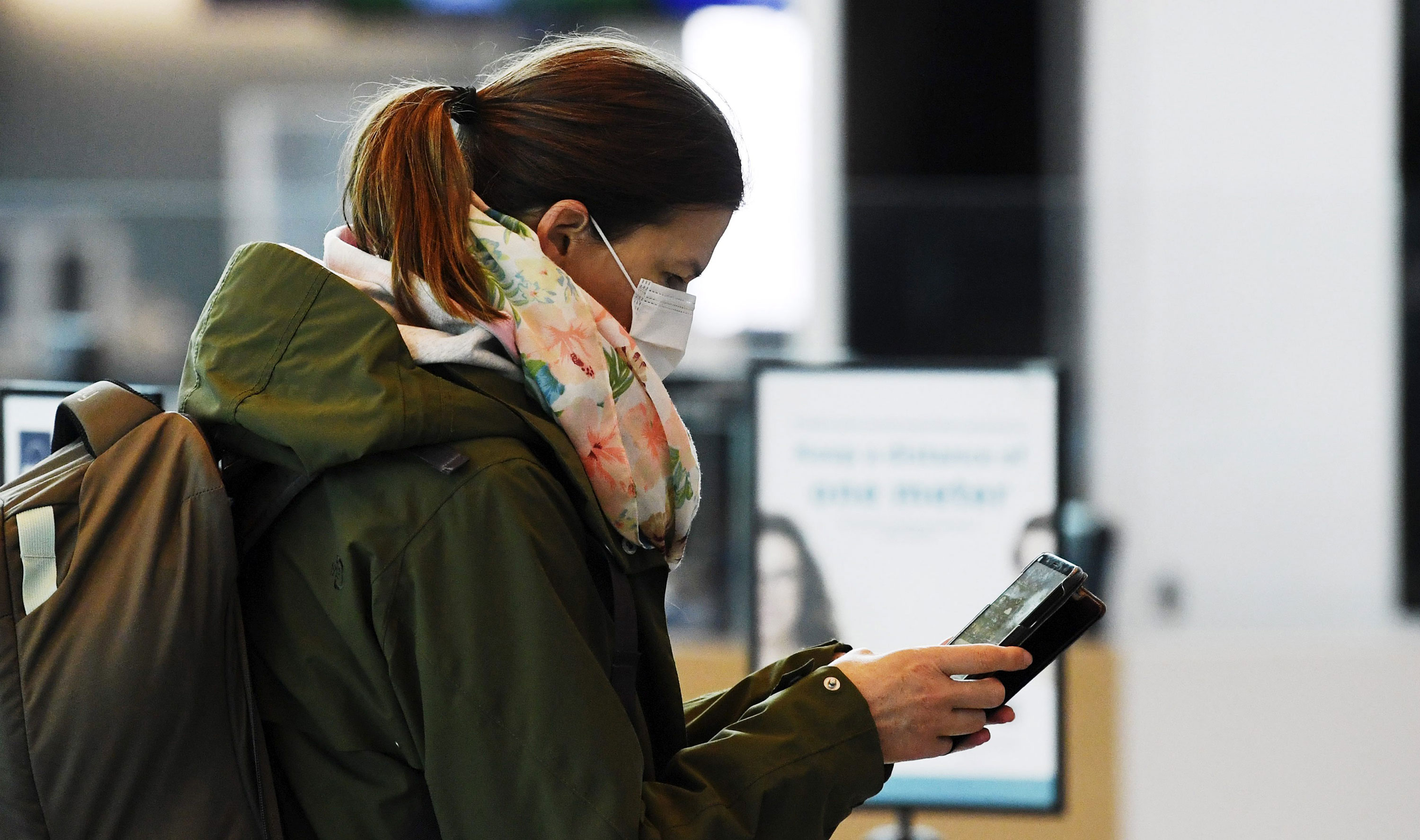 A passenger looks at her phone at the Helsinki International Airport in Vantaa, Finland, on May 13.