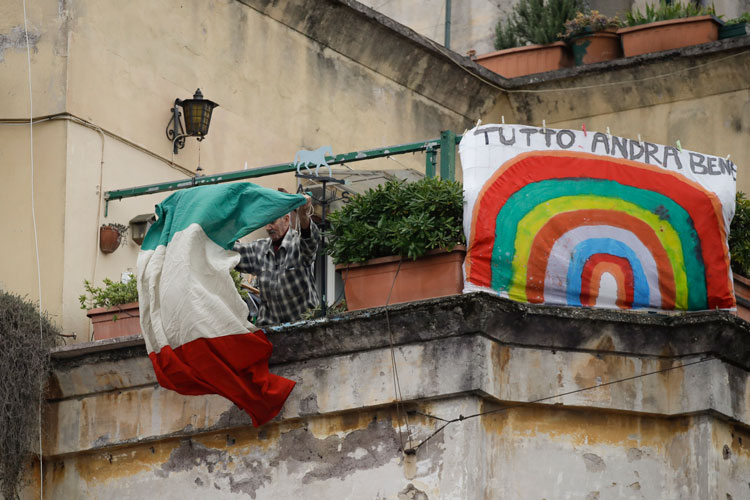 A man unfolds an Italian flag as he stands next to a banner reading everything will be alright, at the Garbatella neighborhood, in Rome, Saturday, March 14.