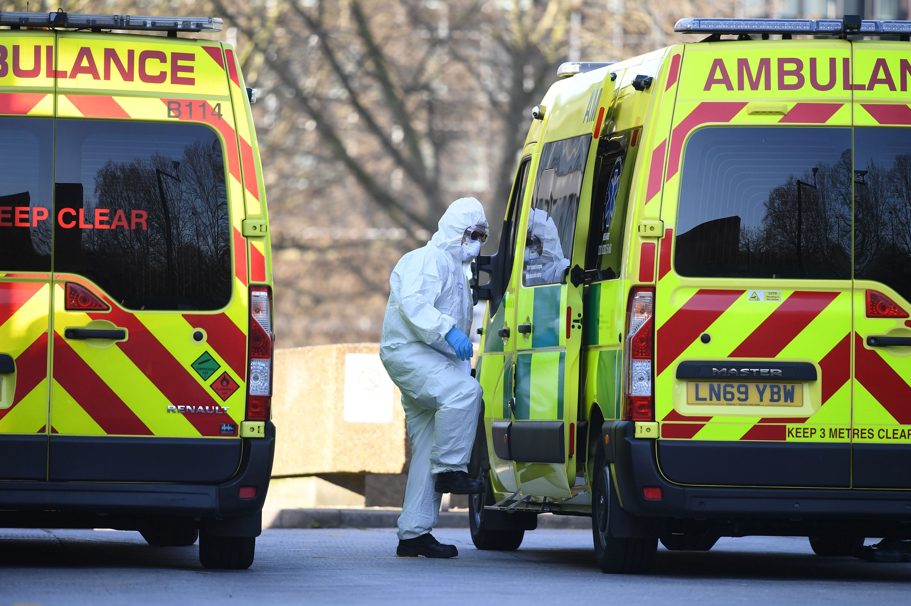 A member of the ambulance service transports a patient into an ambulance at St Thomas' Hospital in London on March 24.