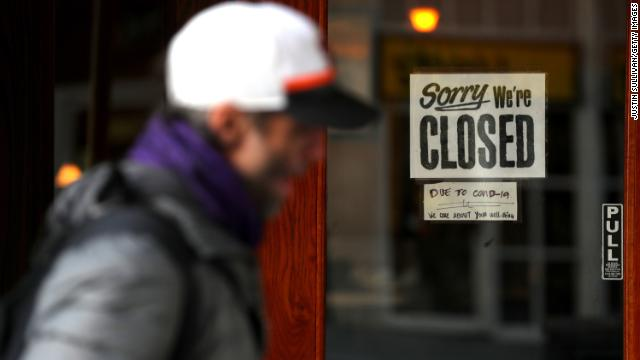 A pedestrian walks by a 'closed' sign on the door of a restaurant on March 17, in San Francisco, California.