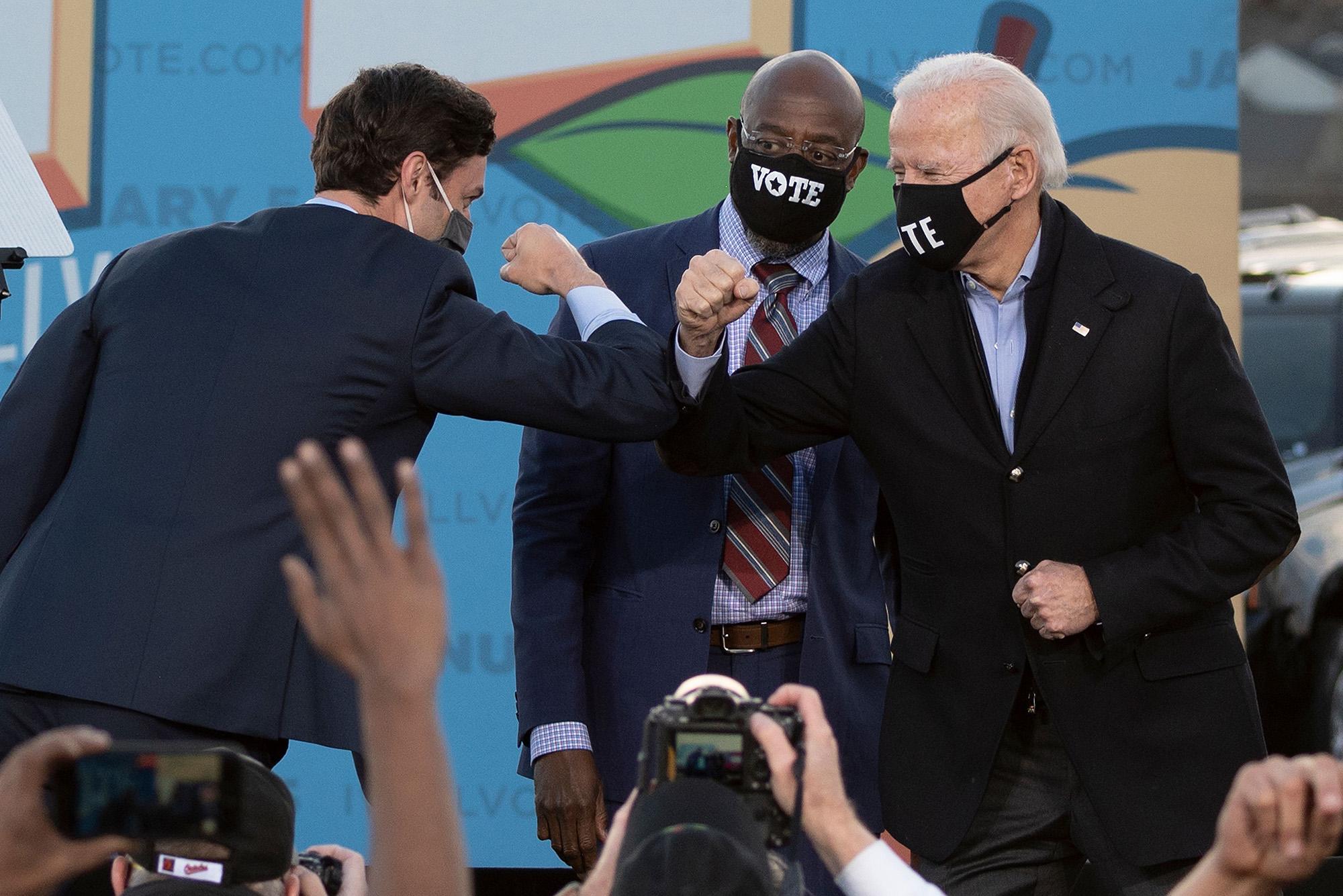 Democratic candidates for Senate Jon Ossoff, Raphael Warnock, and U.S. President-elect Joe Biden bump elbows on stage during a rally outside Center Parc Stadium in Atlanta, Georgia, on January 4.