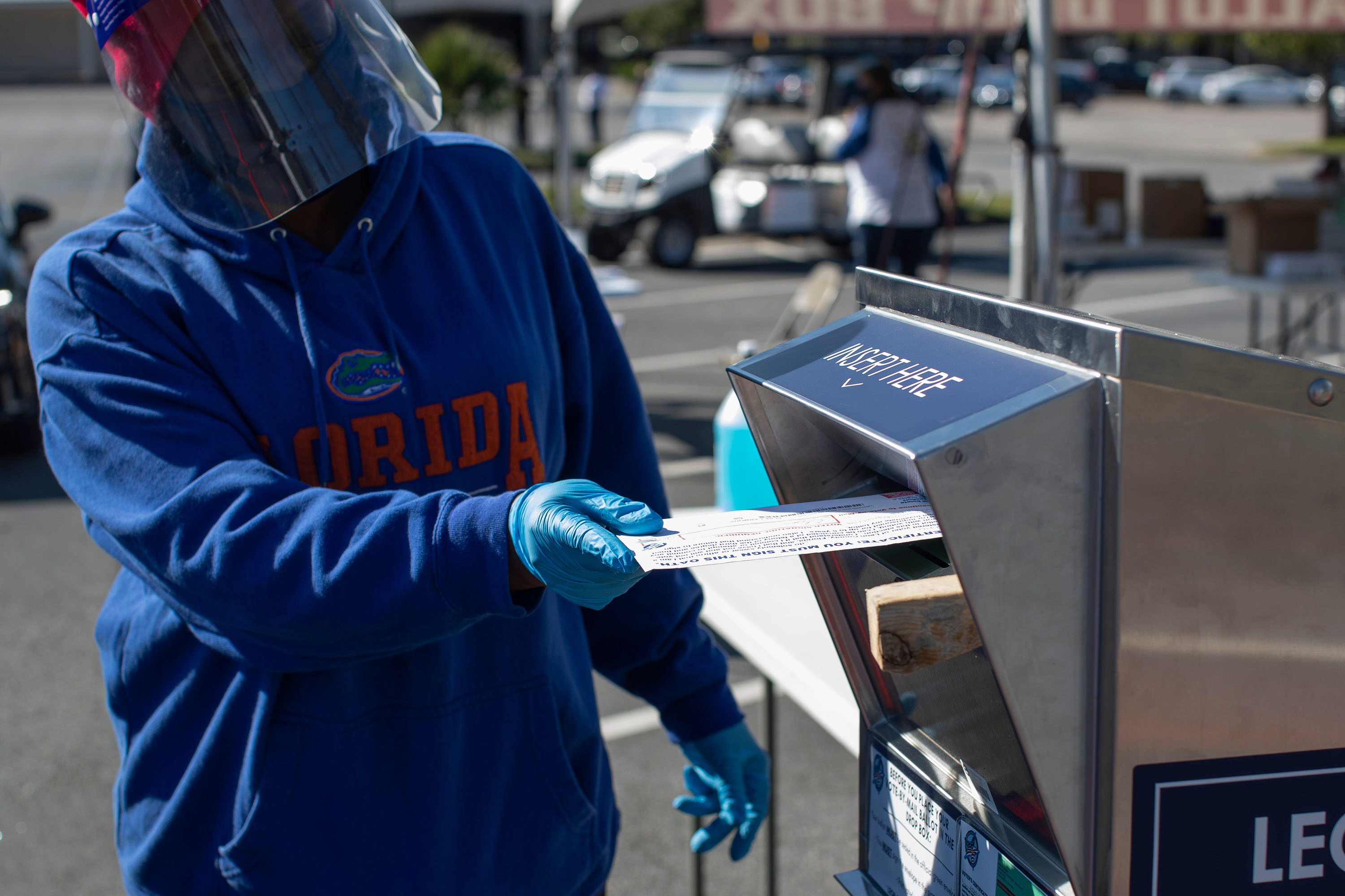 A poll worker collects vote-by-mail ballots at a drive-thru system set up in the parking lot of the Leon County Supervisor of Elections Office in Tallahassee, Florida, on Monday, November 2.