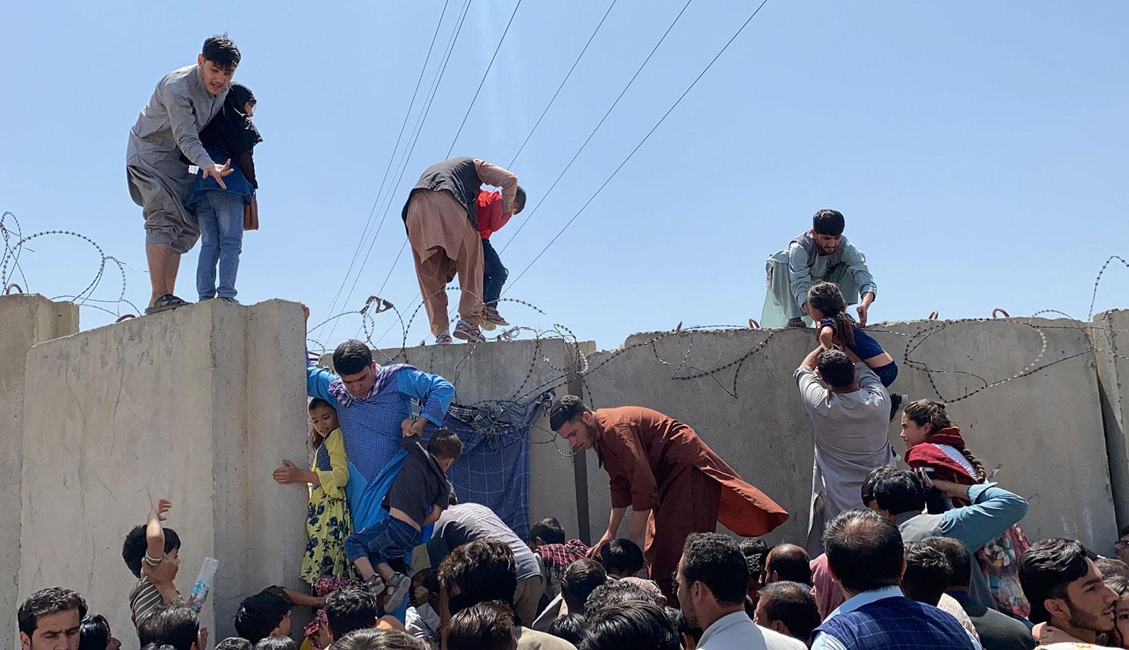 People struggle to cross the boundary wall of Kabul's Hamid Karzai internationalairport on August 16.