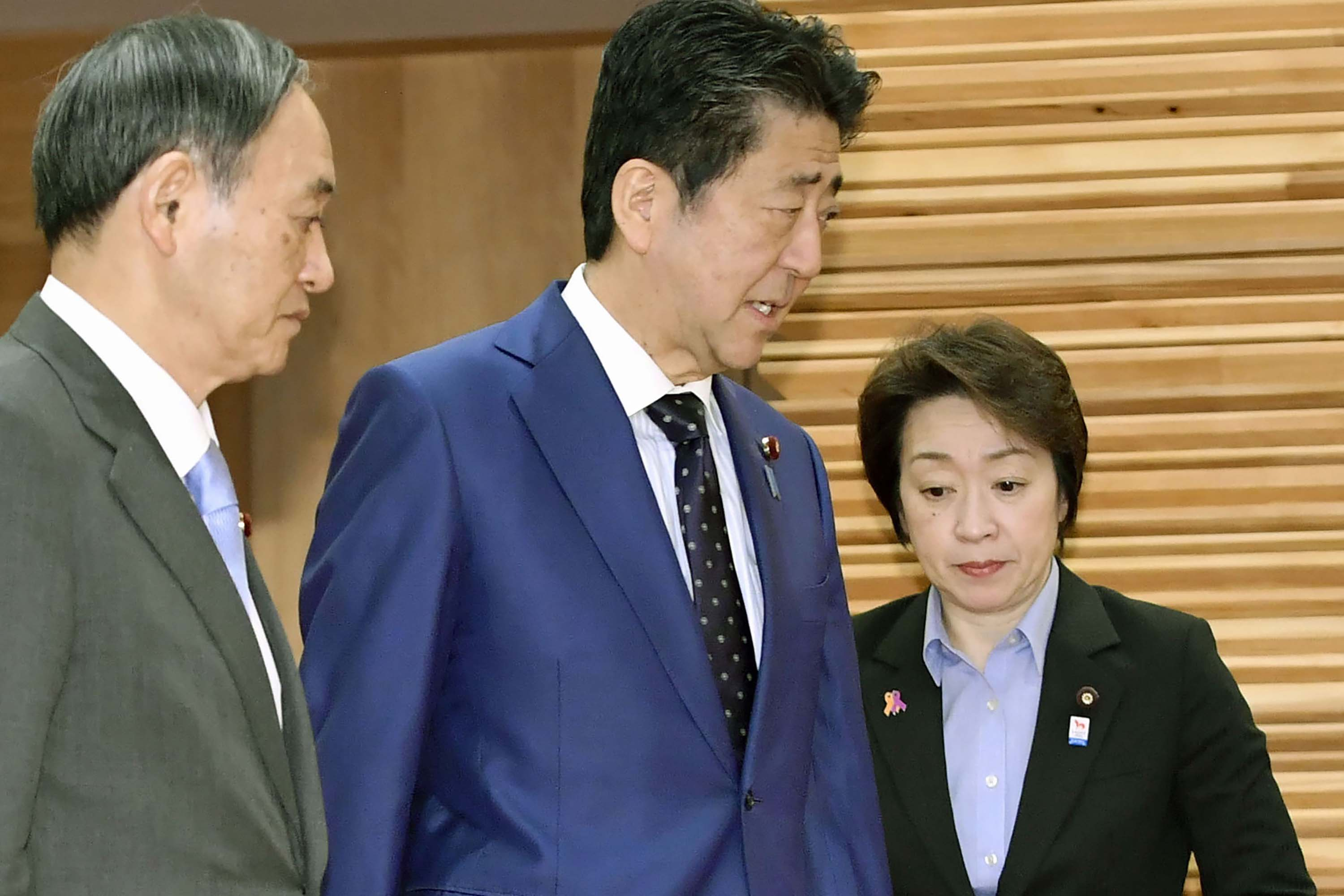 Japanese Prime Minister Shinzo Abe, center, walks past Olympic Minister Seiko Hashimoto, right, to attend a cabinet meeting at his official residence in Tokyo on Tuesday, March 24.