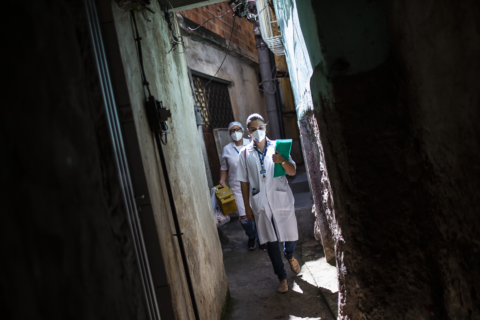Health agents of the City of Rio de Janeiro walk in an alley of Favela da Mangueira on September 3.