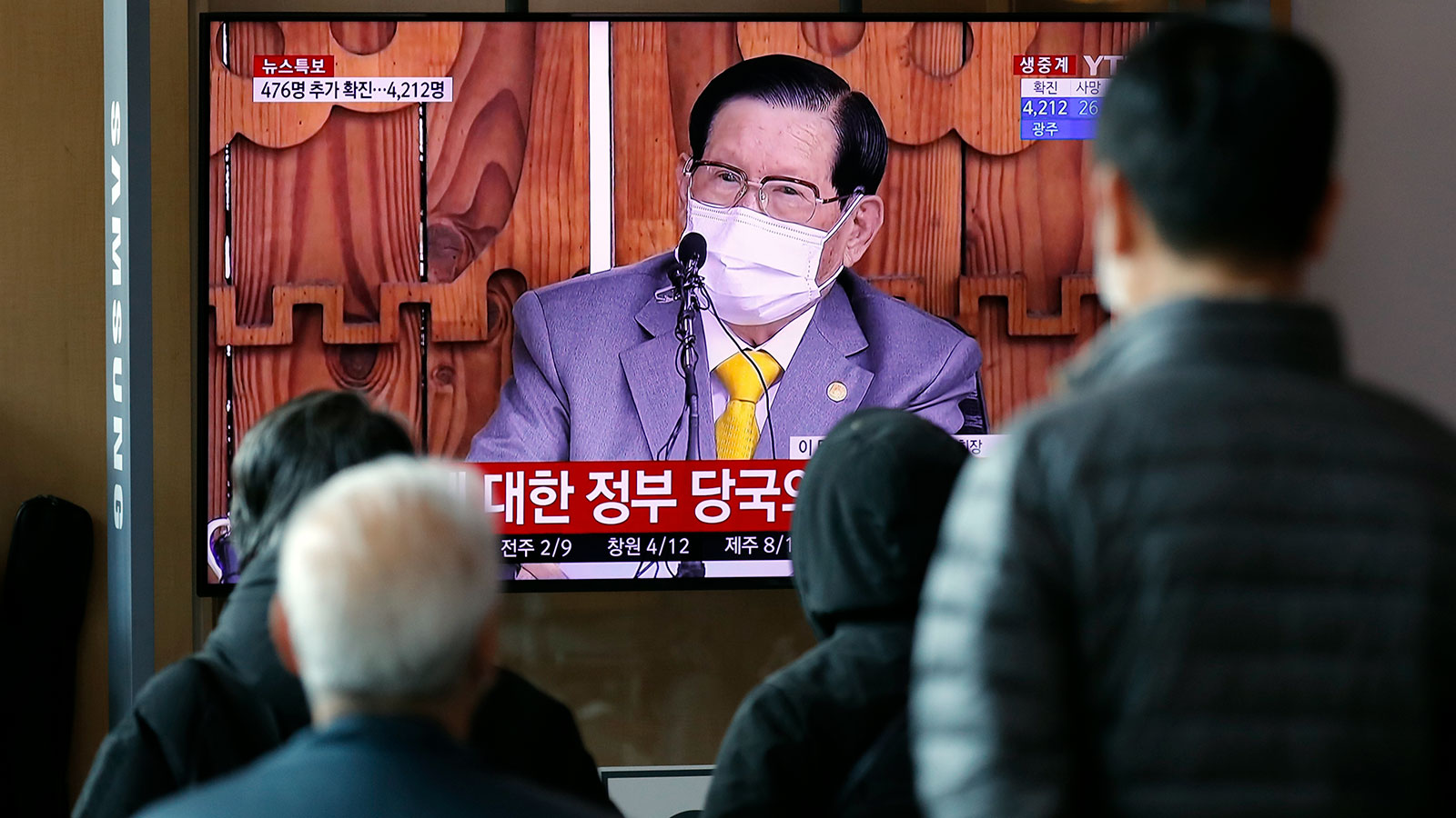 People watch a TV screen showing a live broadcast reporting about Lee Man-hee, a leader of Shincheonji Church of Jesus, at the Seoul Railway Station in Seoul on March 2.