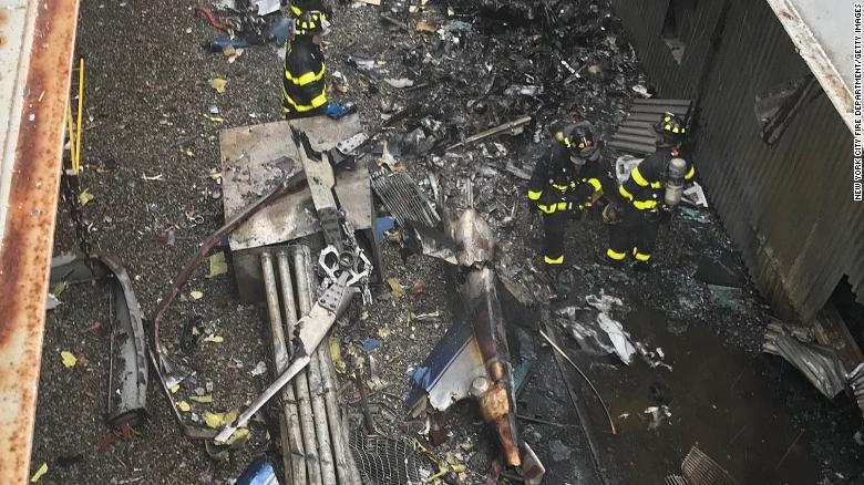 In this handout photo provided by the New York City Fire Department, firefighters work on the roof of 787 Seventh Ave. after a helicopter crashed there on June 10, 2019 in New York City.