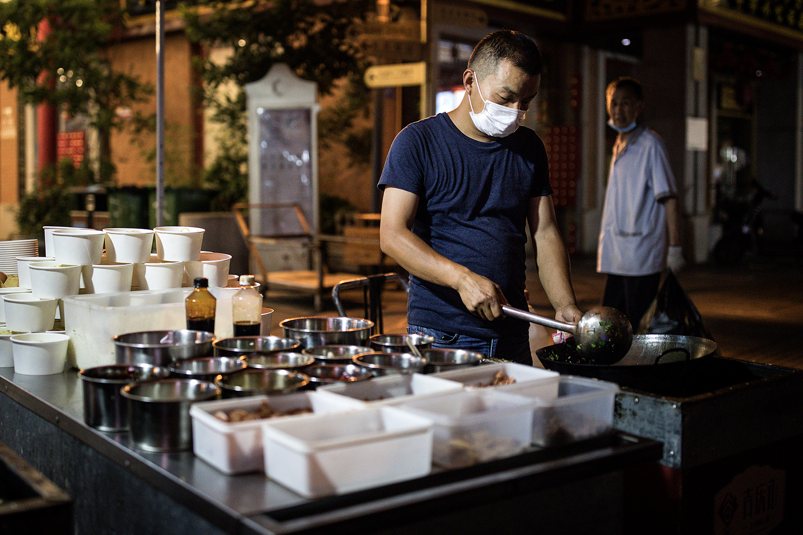A man cooks outside of the restaurant on Jiqing street on June 5, in Wuhan, China.