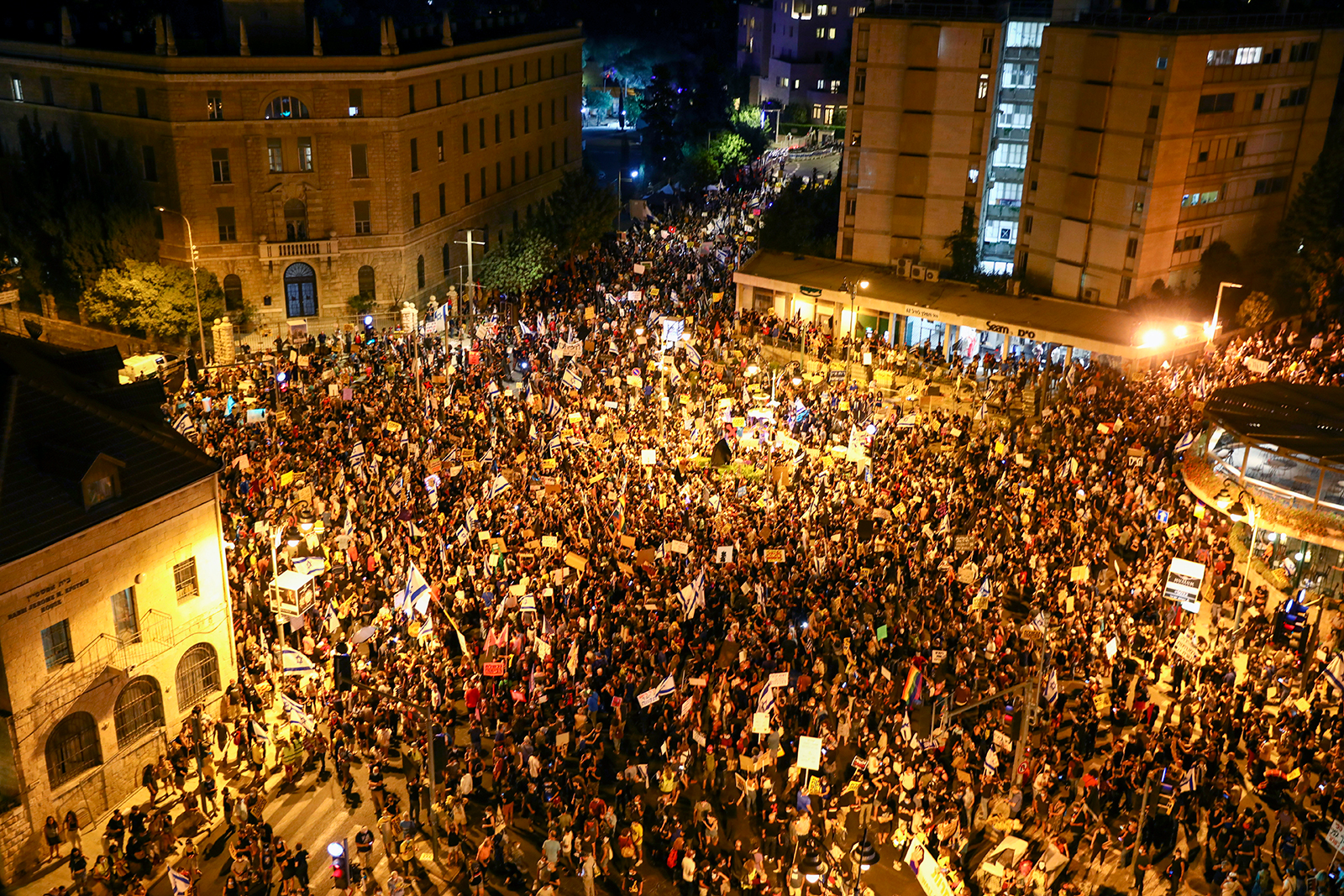 Thousands of protesters chant slogans and hold signs during a protest against Israel's Prime Minister Benjamin Netanyahu outside his residence in Jerusalem, on August 1.