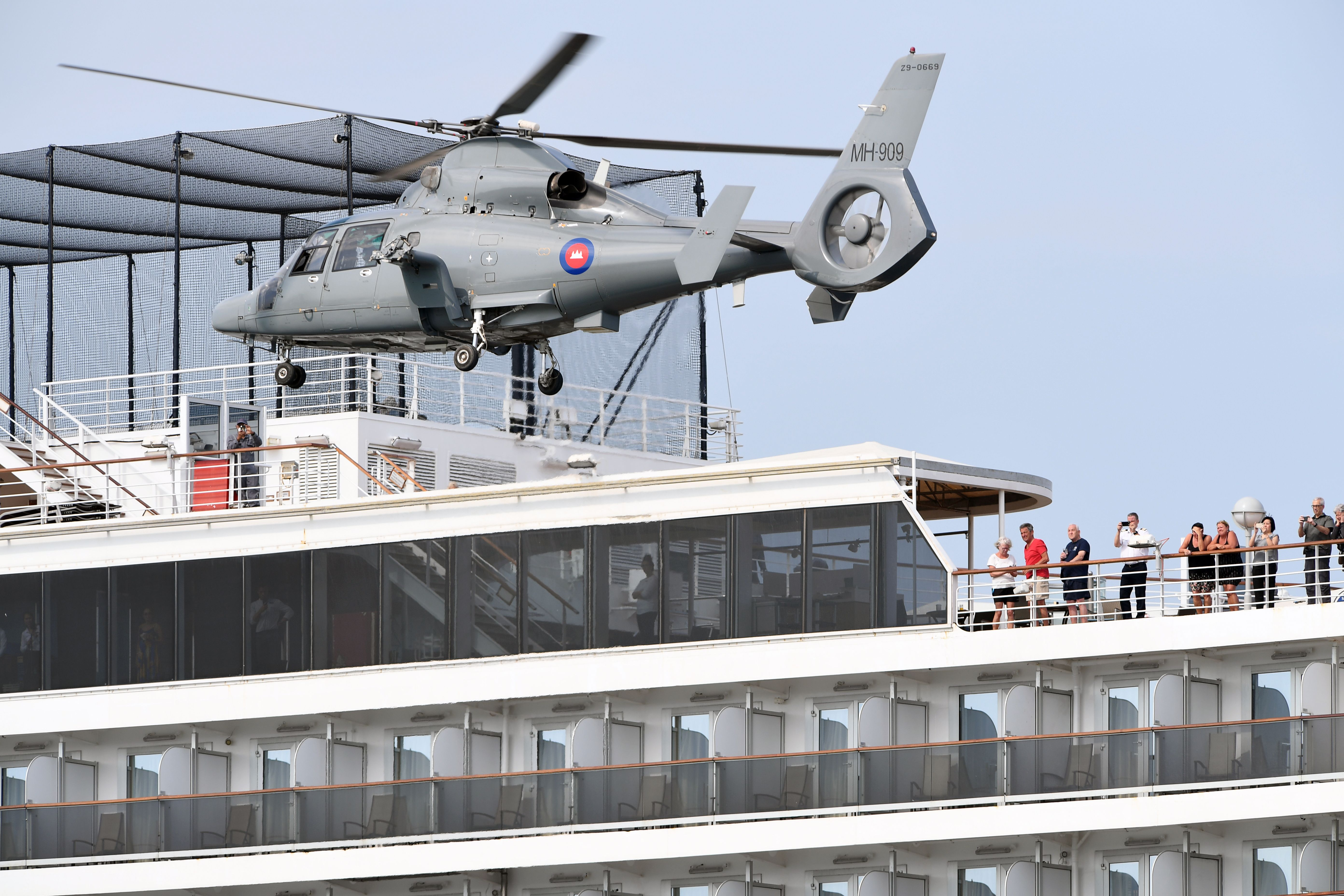 People on a deck of the Westerdam cruise ship watch a helicopter take off in Sihanoukville.