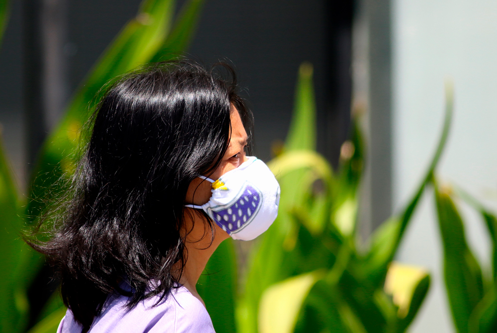 A woman wears a mask as a precaution against the coronavirus in Honolulu on Tuesday, April 7.