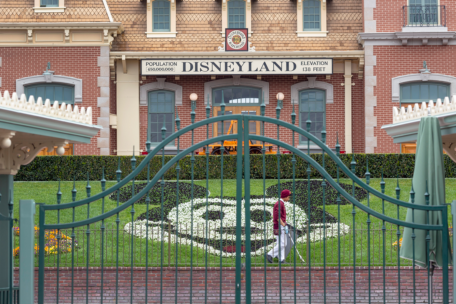 An employee cleans the grounds behind the closed gates of Disneyland Park in Anaheim, California, on March 14.