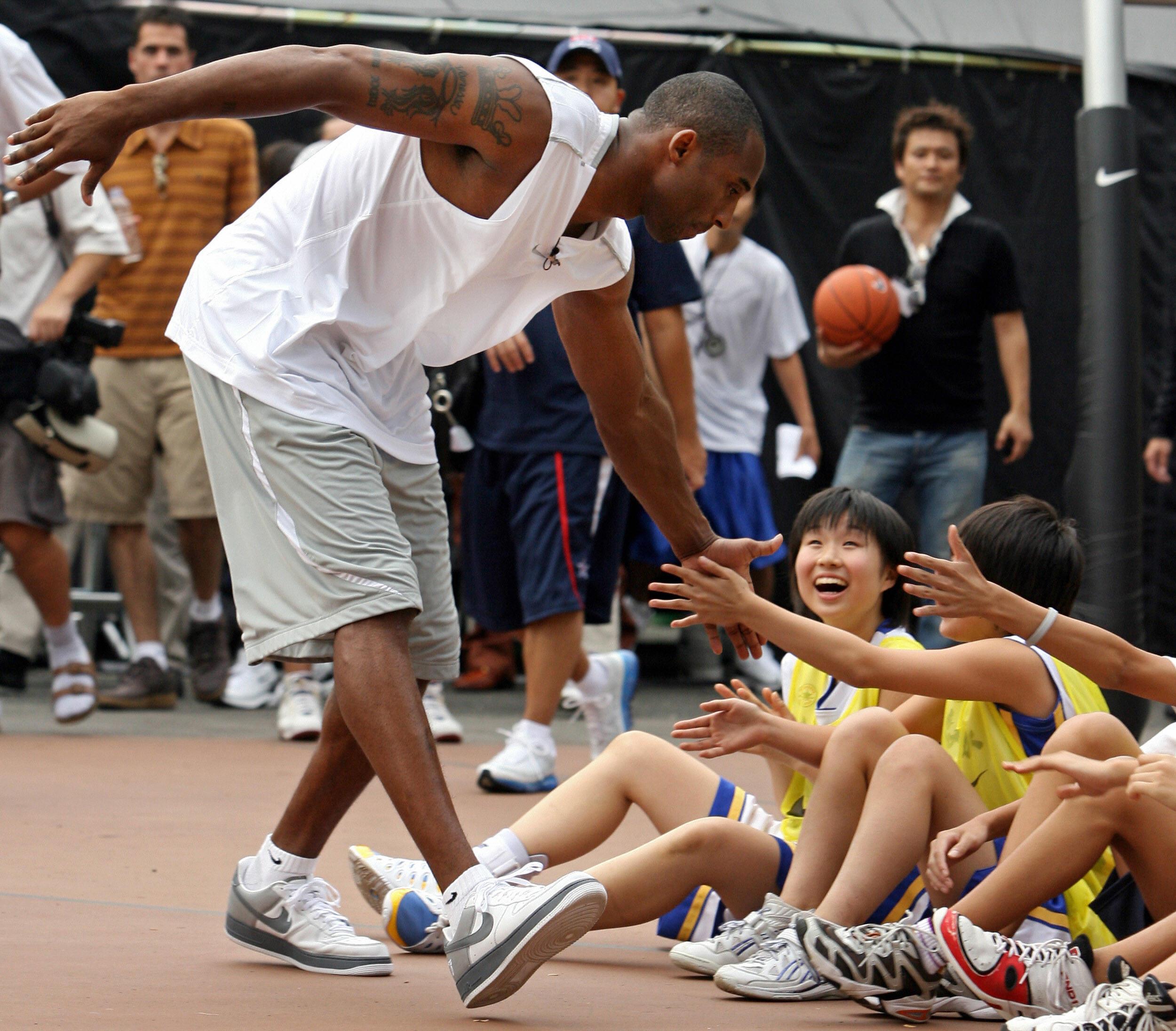 Kobe Bryant greets junior basketball players in Tokyo in September 2006.