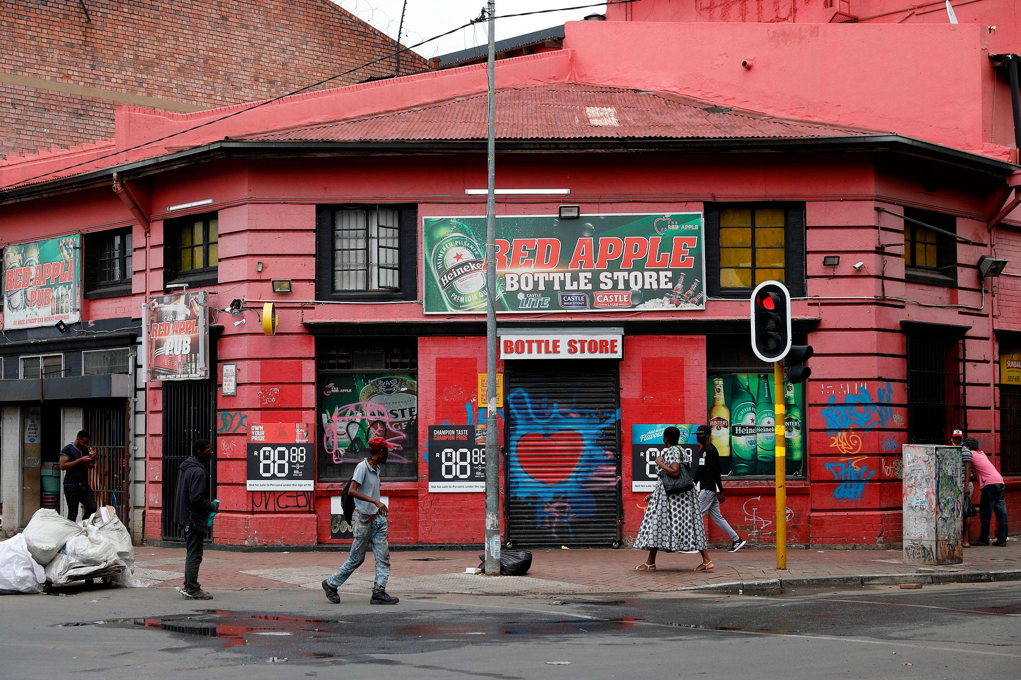 A man walks past a closed liquor store in Newtown, Johannesburg, on December 29, 2020.