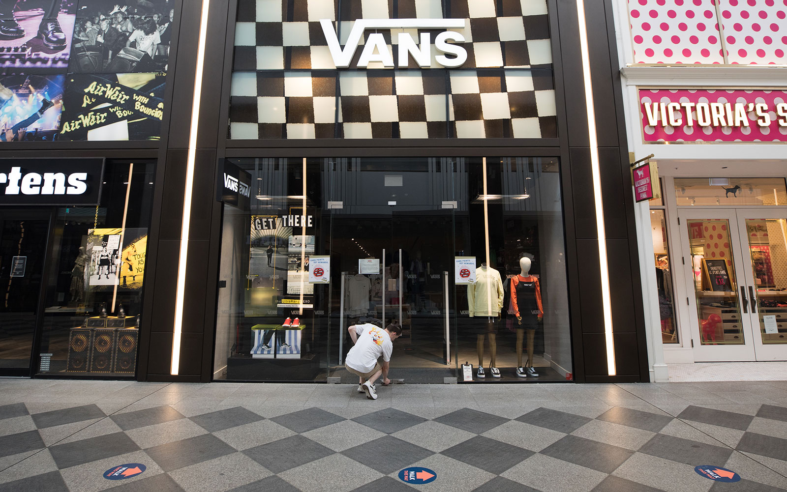 An employee locks a Vans Inc footwear store at the Westgate shopping centre in Oxford on Wednesday, May 27. Retail outlets can reopen starting June 15 as long as they comply with government coronavirus-secure guidelines.