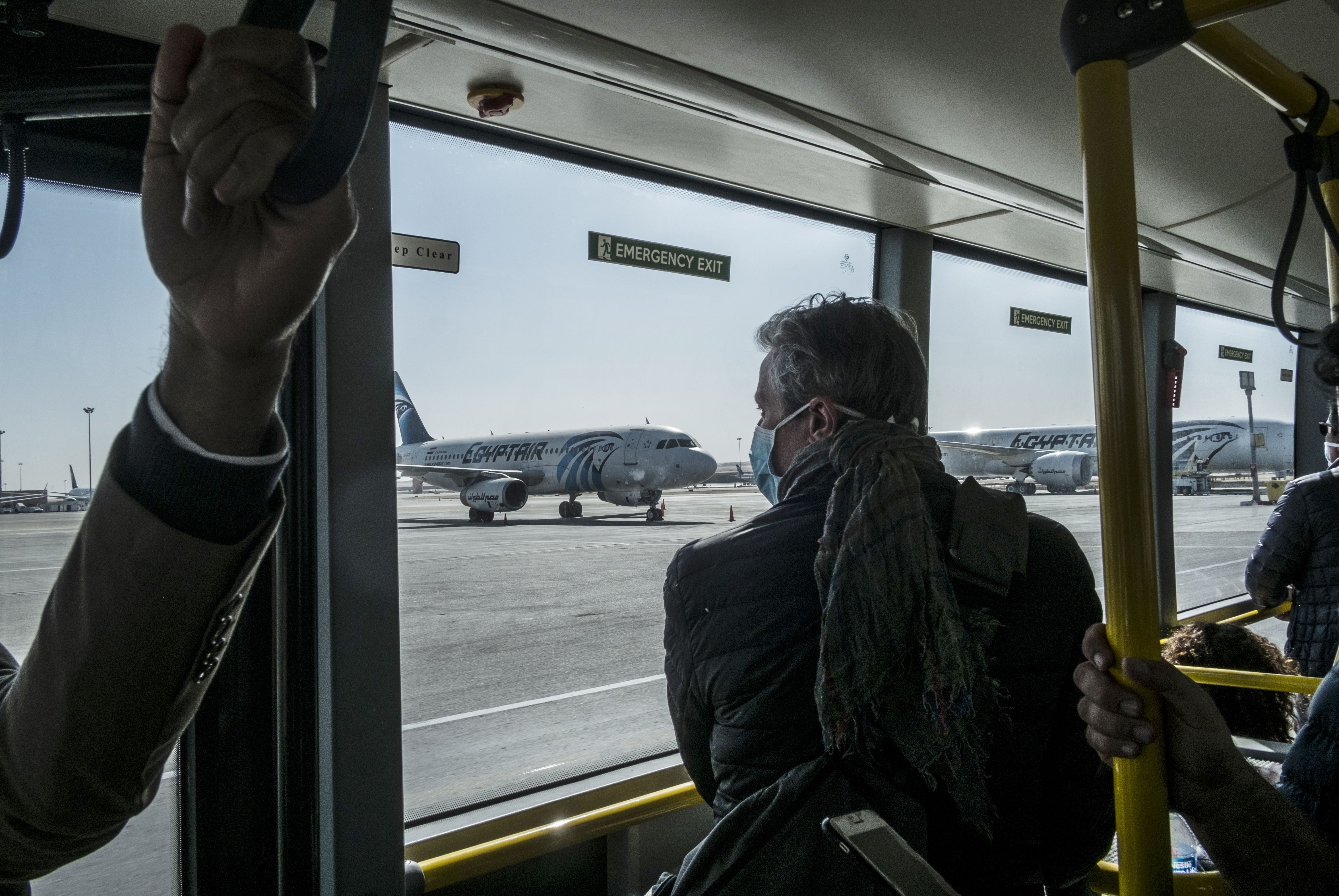 A passenger wearing a protective mask rides a bus at Upper Egypt's Luxor airport to the arrivals hall on Tuesday, March 10.