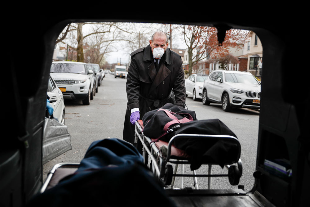 Funeral director Tom Cheeseman loads a body into his van in Brooklyn, New York, after making a house call on Friday, April 3. The Associated Press spent a day on the road with Cheeseman, who is overwhelmed by demand due to the coronavirus outbreak.