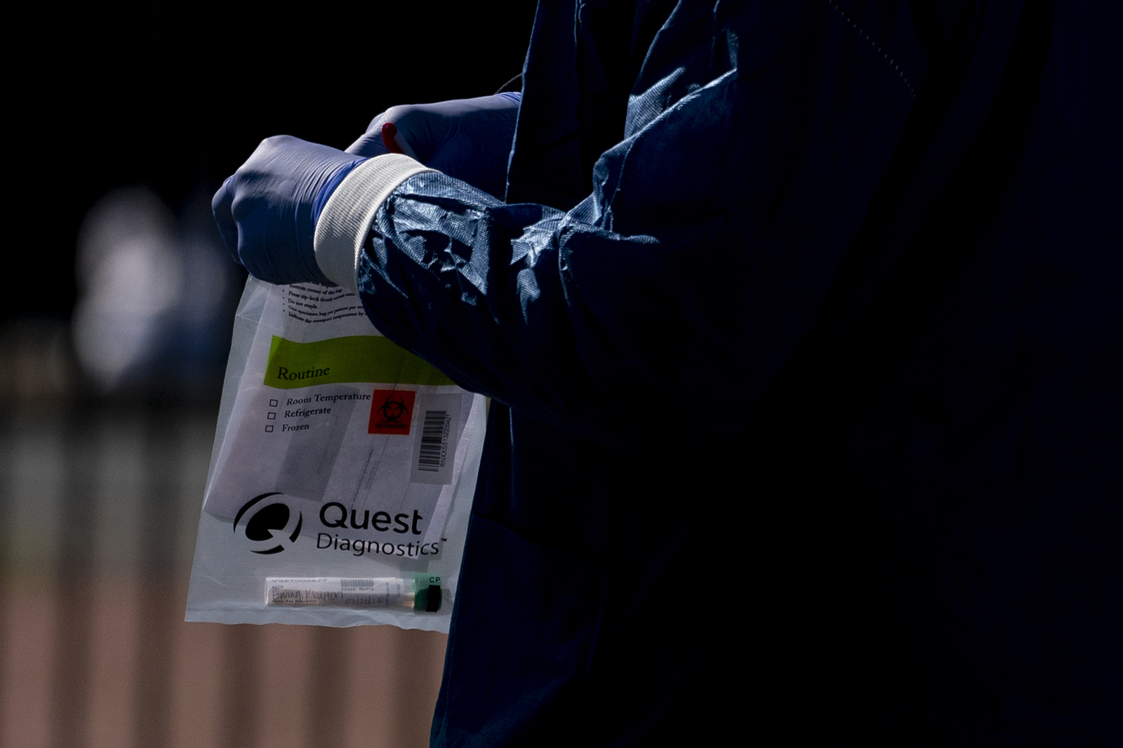 A Children's National Hospital healthcare worker holds a Quest Diagnostics bag containing a Covid-19 swab at a coronavirus drive-thru testing site at Trinity Washington University in Washington, D.C., on Thursday, April 2, 2020.